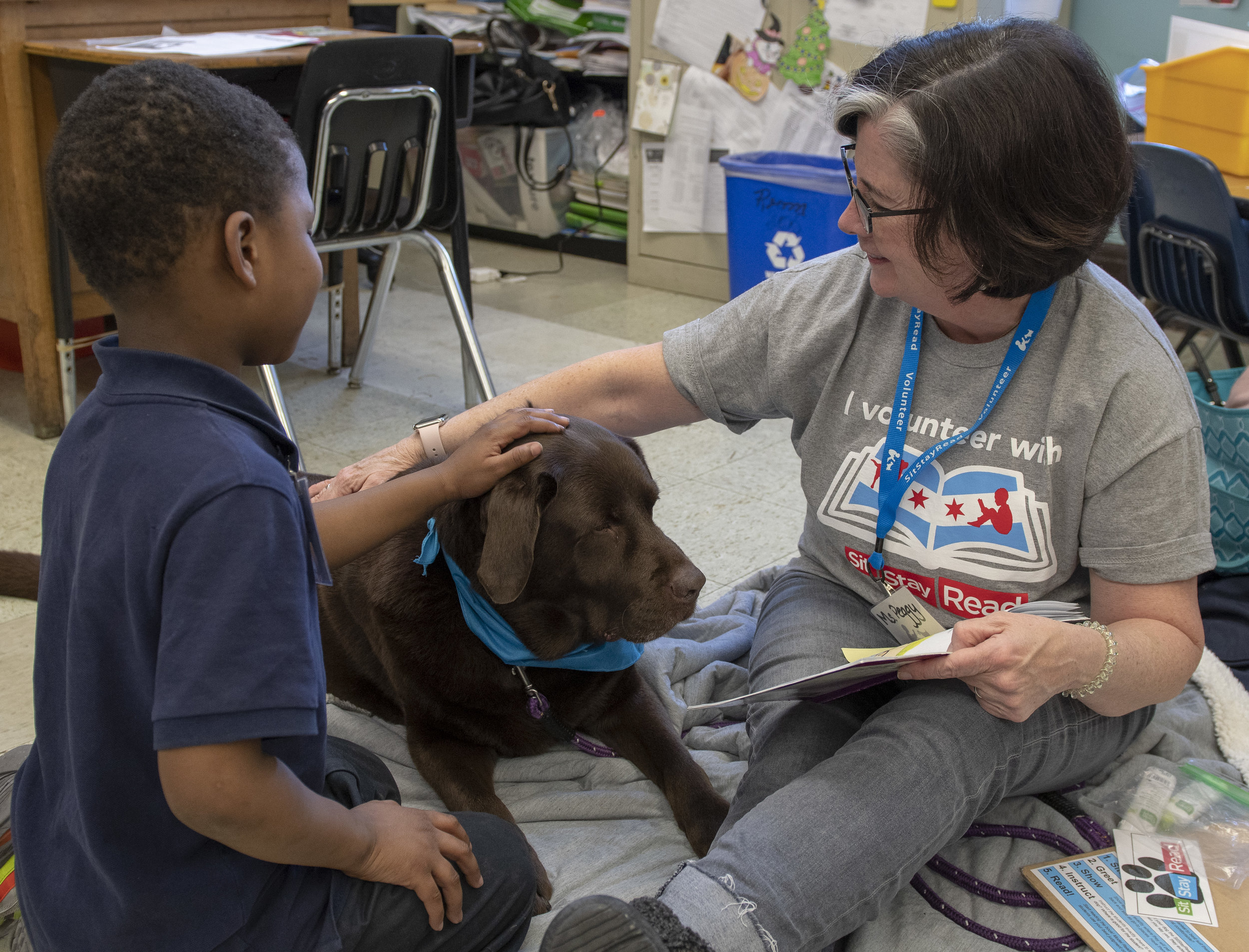 Dog Team volunteer Peggy and her Certified Reading Assistance Dog Woodrow visit with a student in a Tail Blazers program at Melody Elementary. (J. Sall)