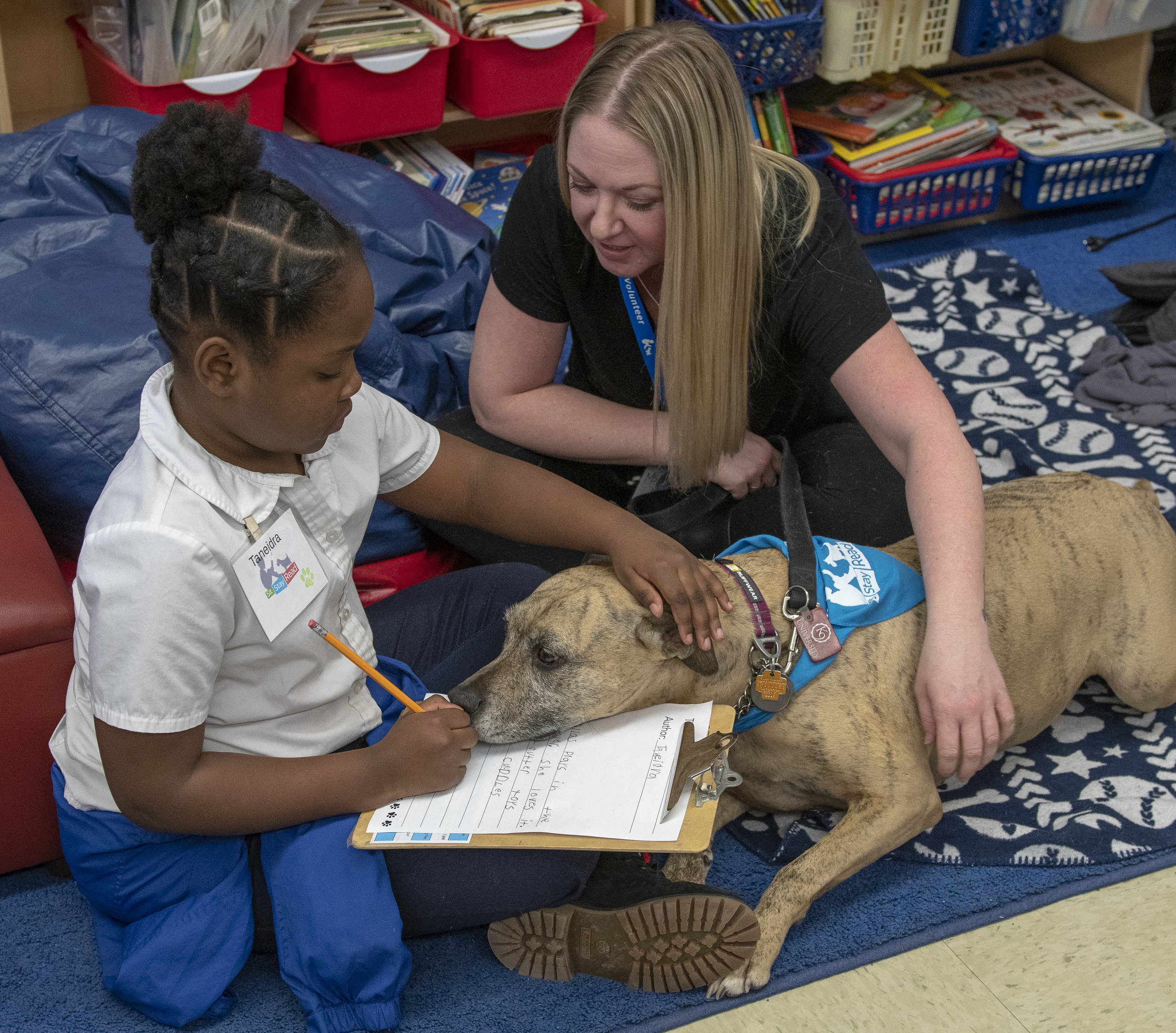 Second-grader Taneidra writing her story with the help of Dog Team volunteer Harmony and her Certified Reading Assistance Dog Dallas. (J. Sall)