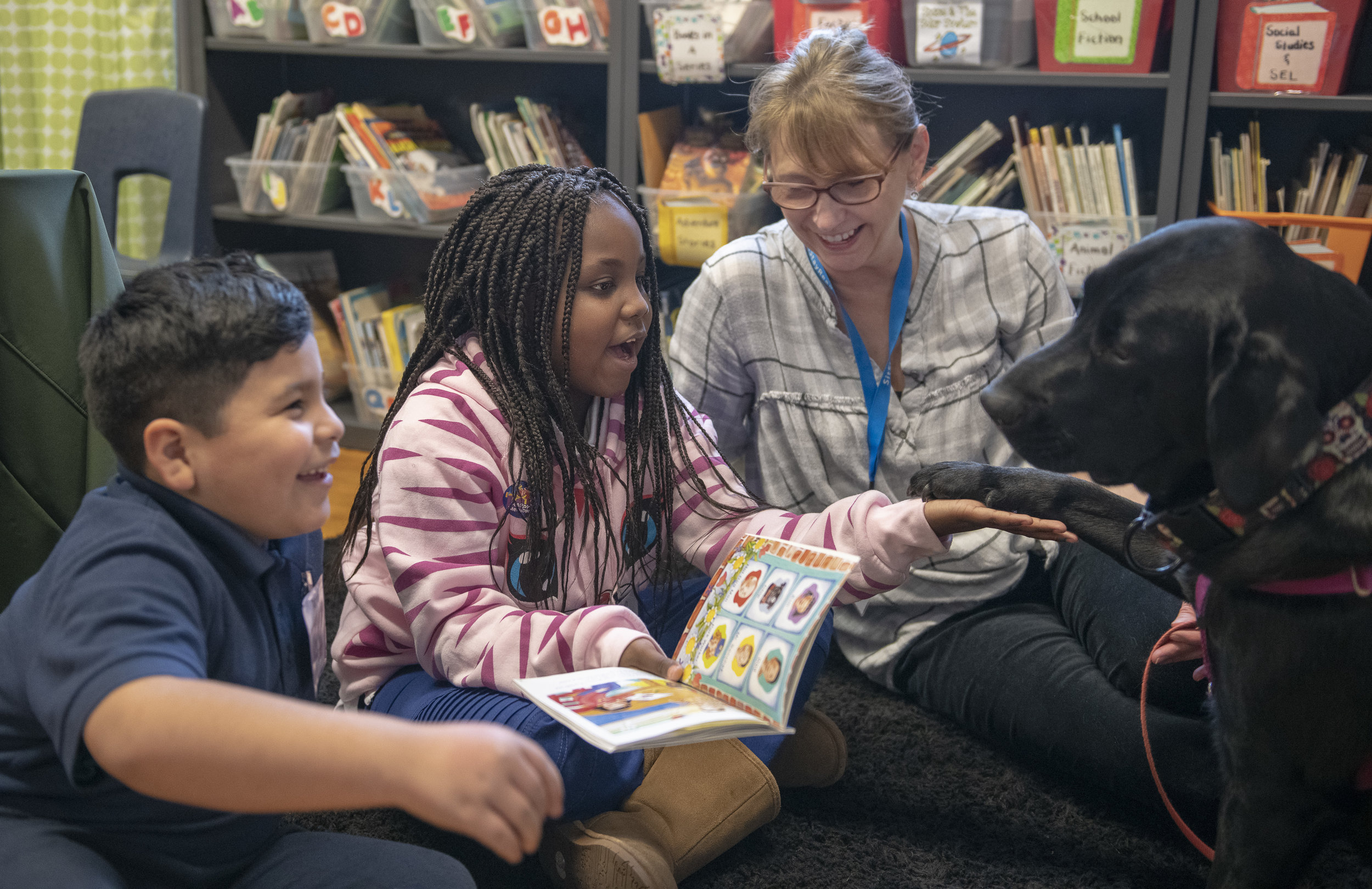 Dog Team volunteer Lisa Sall with her Certified Reading Assistance Dog Jinks reading with students in a Tail Blazers program at Marquette Elementary. (J. Sall)