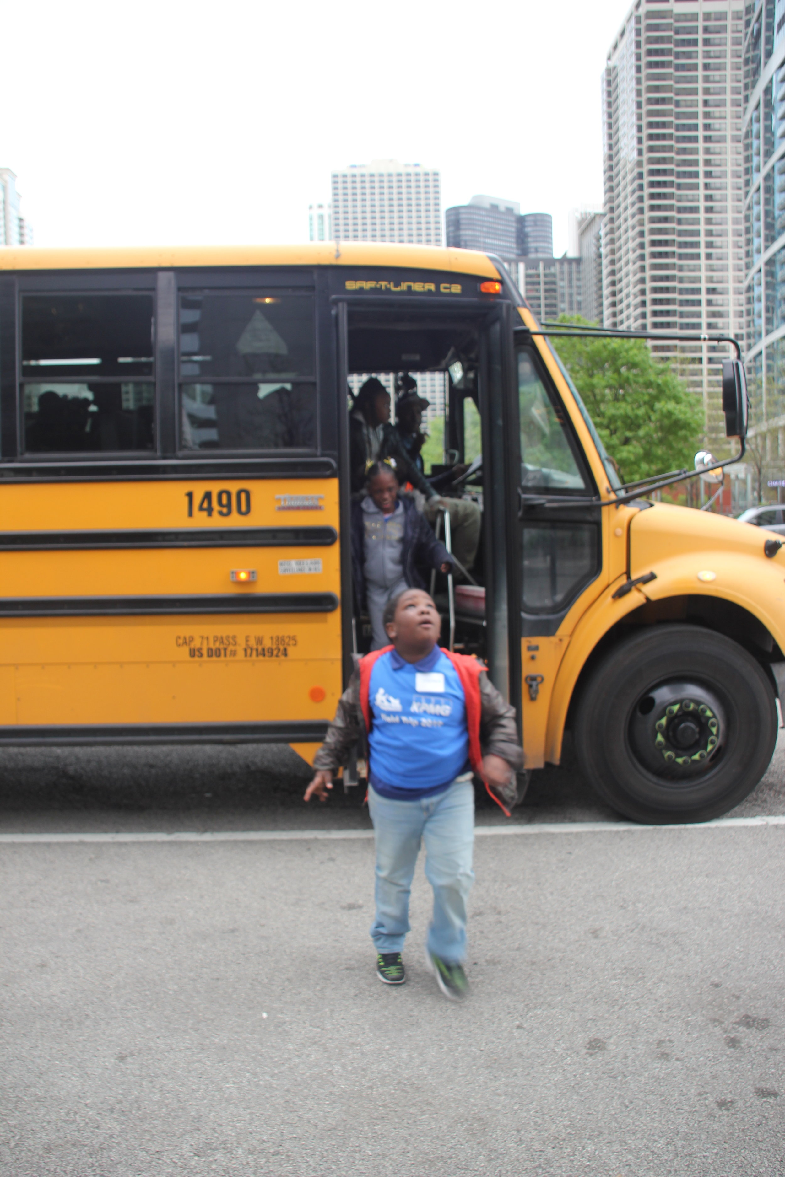 Second-grader Johantes steps off the bus and looks up at the Aon Center, the location of the KPMG offices and their SitStayRead field trip. (M. O'Brien)