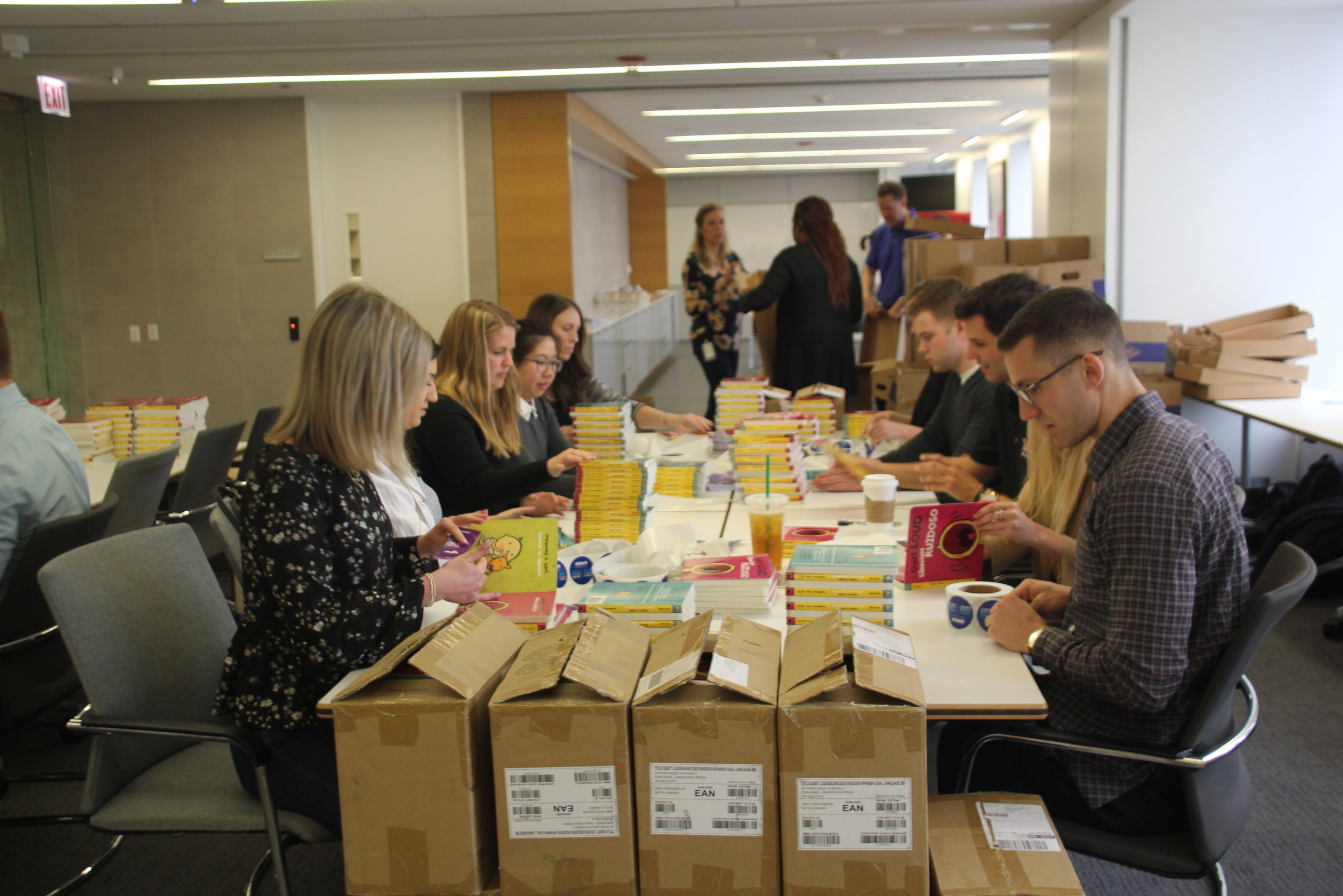 KPMG volunteers busy packing books for upcoming Keep Reading Celebrations. They packed over 10,000 books in five hours! (M. OBrien)