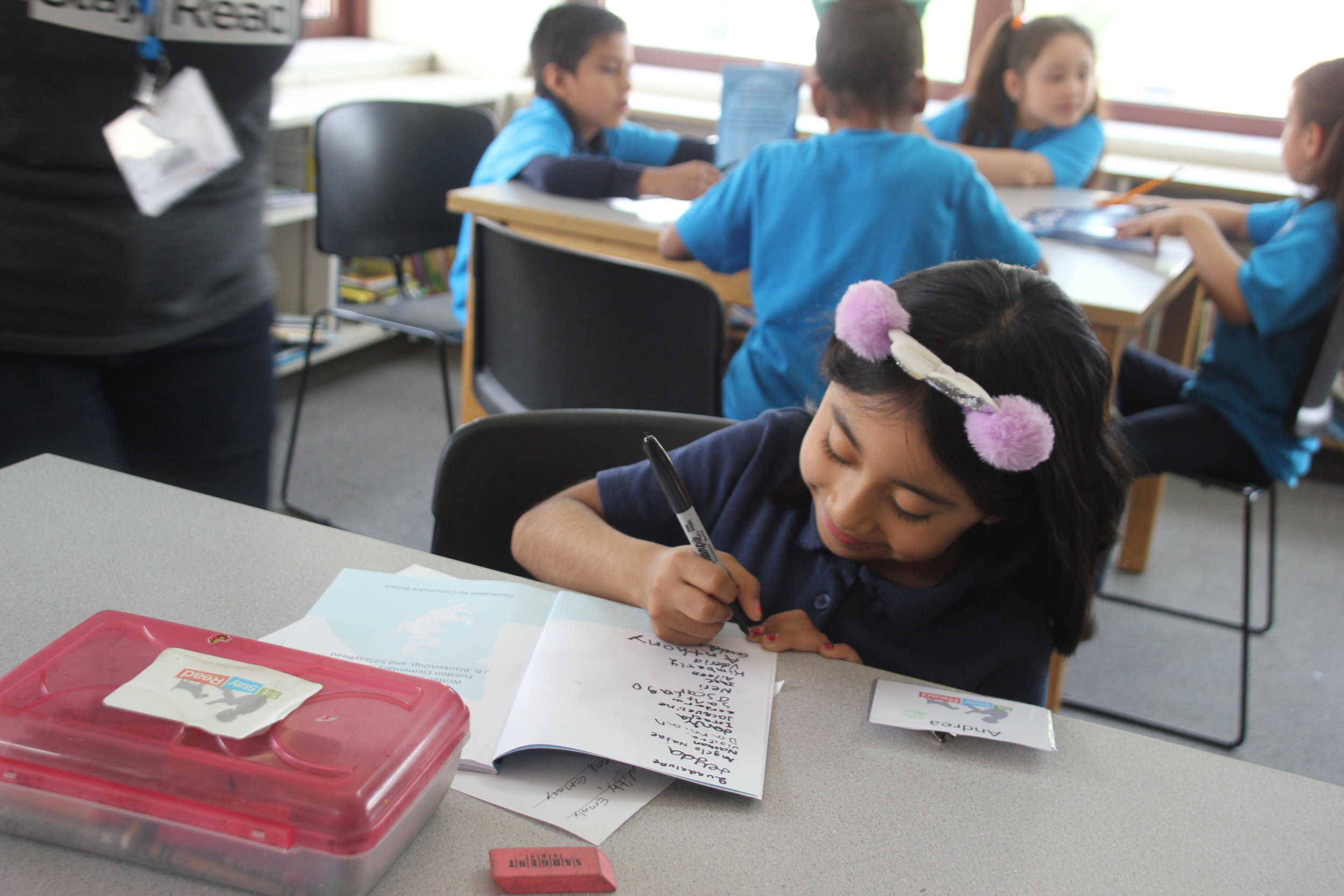 Second grader Andrea signing the book she, and other students, helped create.