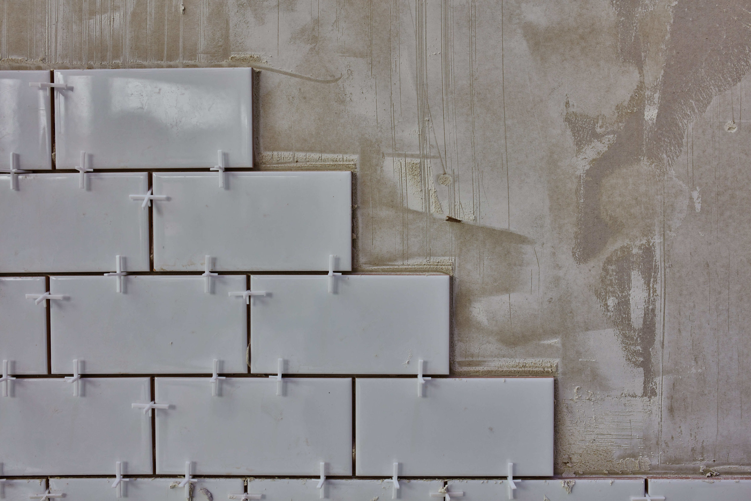 Gray Subway Tiles With Spacers Being Installed as Backsplash (Large Size).jpg