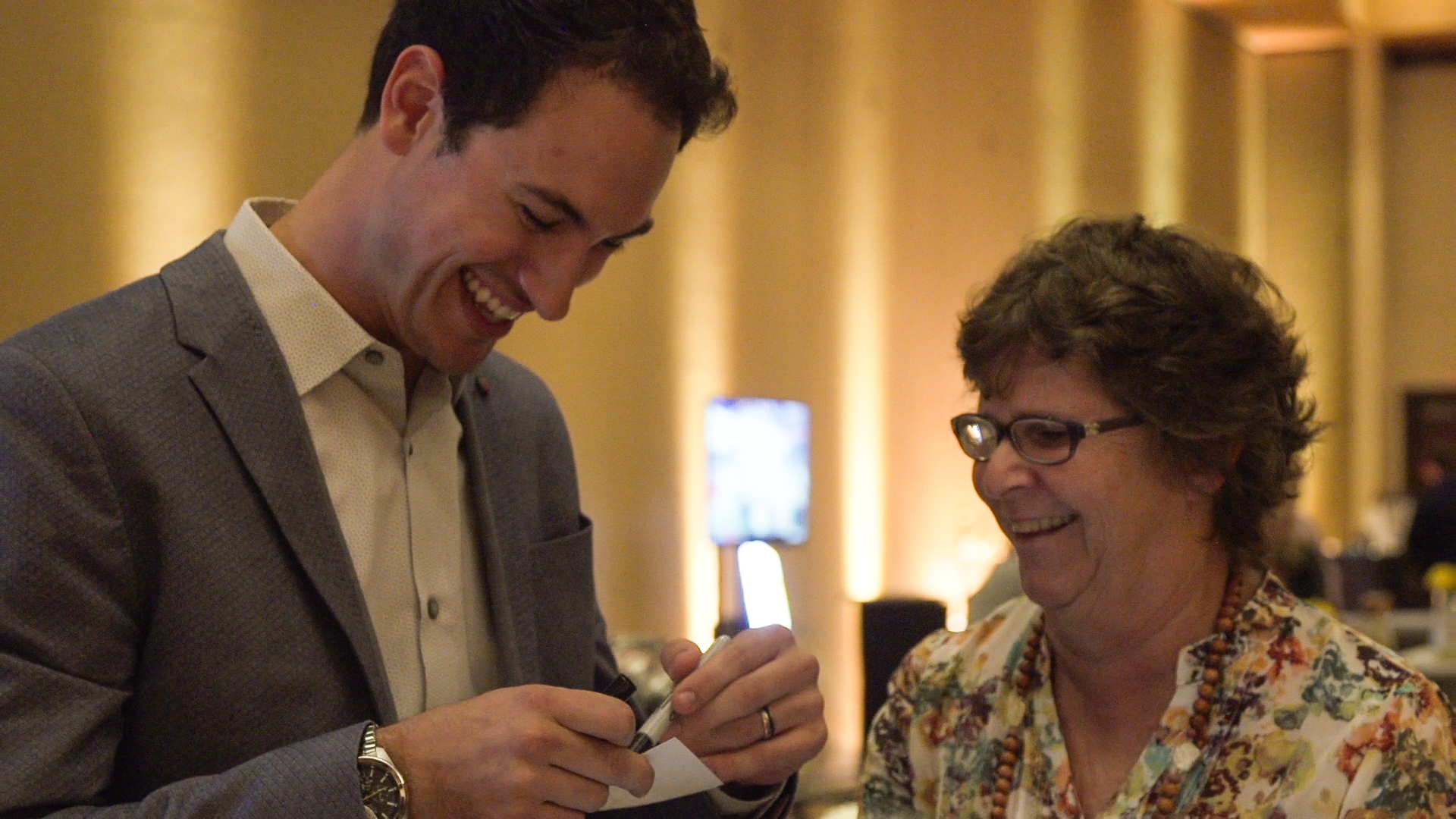 Joey Logano signs a photo for a customer at dinner Saturday night.