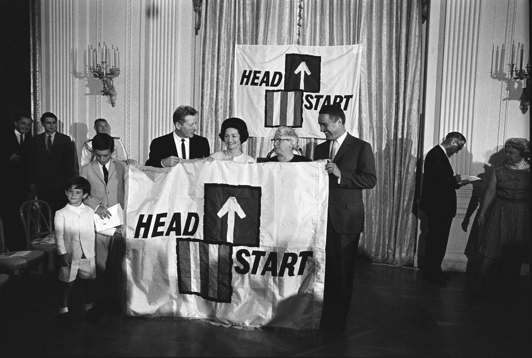 LBJ Library photo, 233-15A-WH65. L-R Timothy Shriver, Robert Shriver, Danny Kaye, Lady Bird Johnson, Mrs. Lou Maginn (Director of a Head Start project in East Fairfield, Vermont), Sargen.