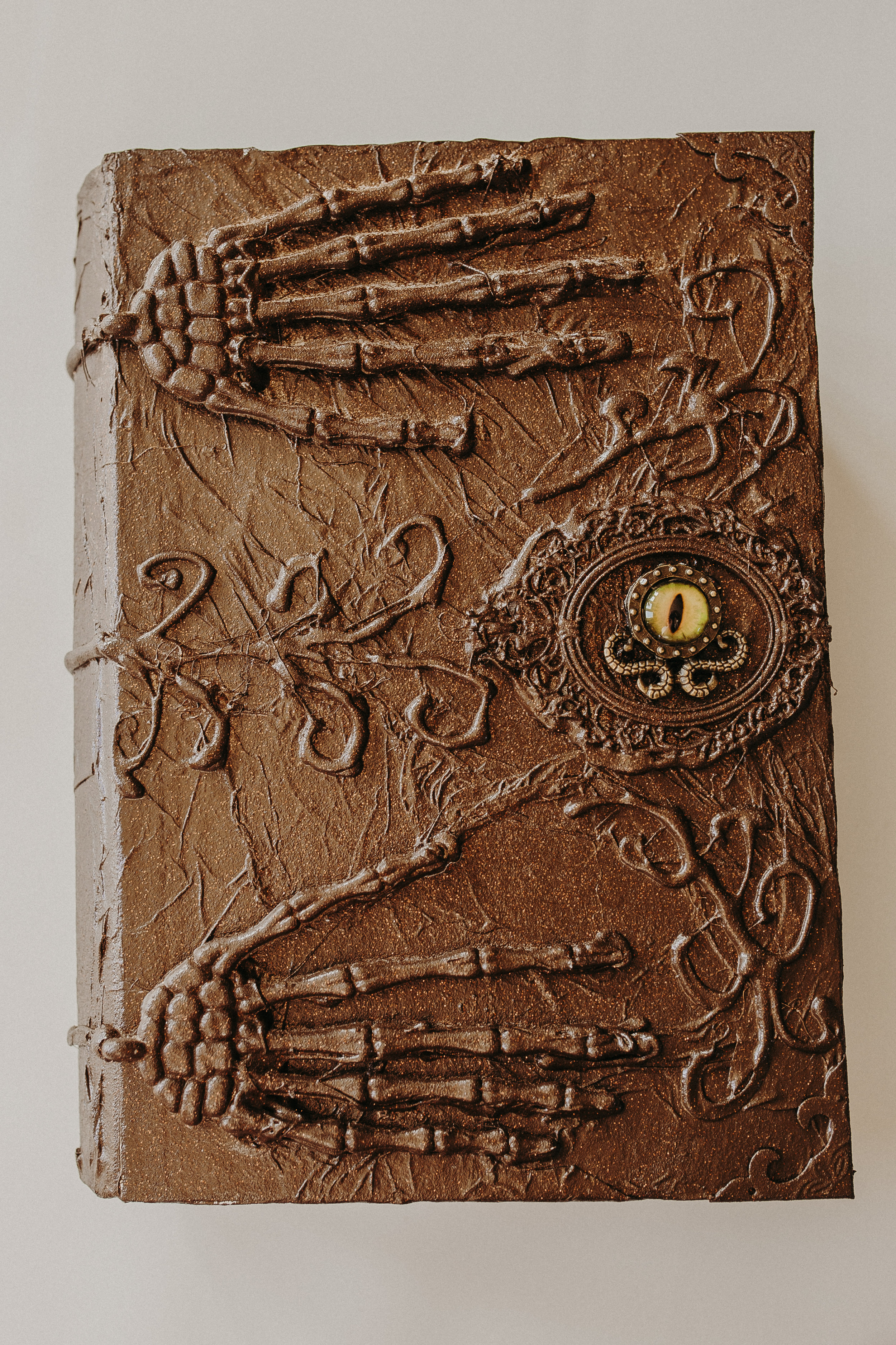 """Step Six: Once your glue has dried completely, paint your book and apply any finishing touches. I left my """"eye"""" until the end so it would stand out more!"""