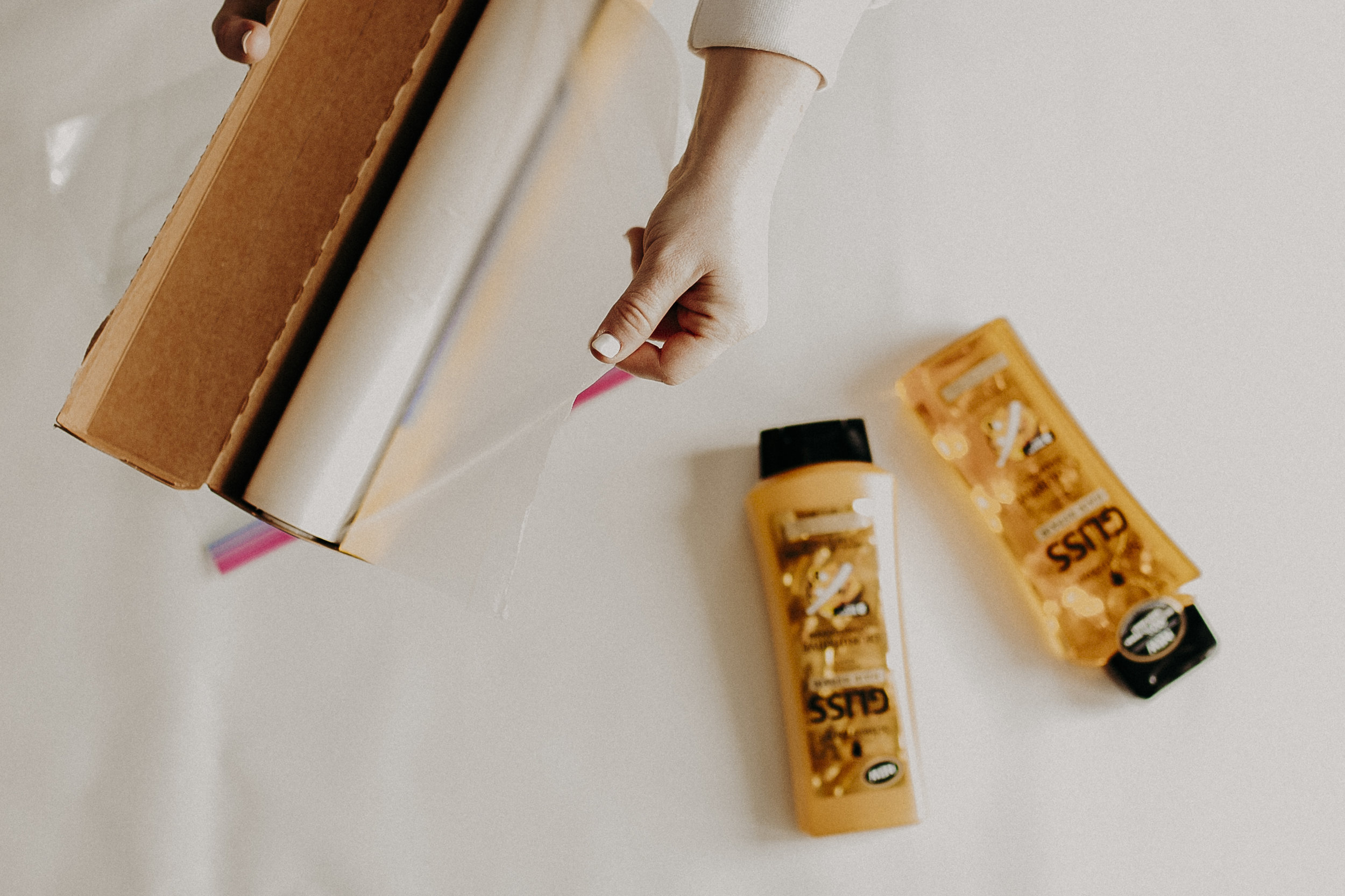 My second tip is how to properly pack your haircare products. There's almost nothing worse than starting a trip, only to realize your shampoo has exploded during flight. You can easily prevent that from happening by applying some plastic food wrap over the opening of your shampoo bottle, then re-attaching your lid.