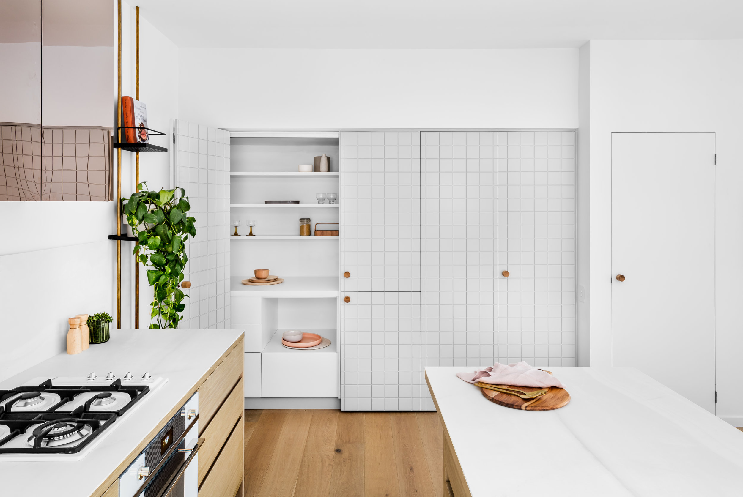 Finishes have aspects of reflectivity and neutrality including brass tapware, cabinetry and rangehood in the kitchen, white walls, white tiles and light grey terrazzo flooring in the bathrooms. Photo -  Maegan Brown .