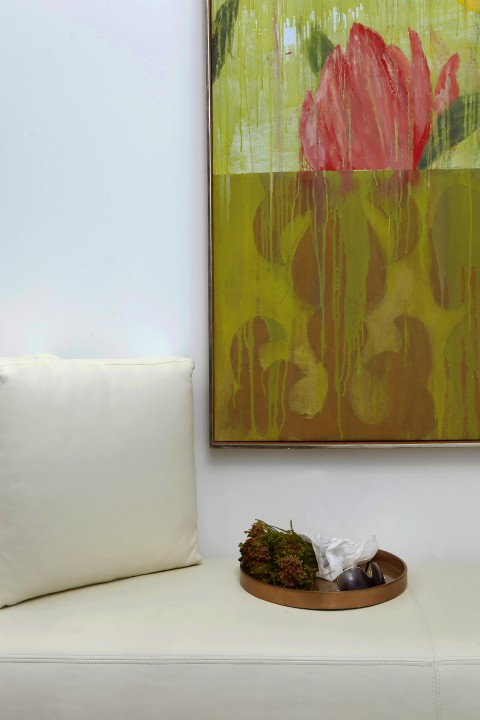 Colorful art acts as a counterpoint to the pristine white walls and furniture.