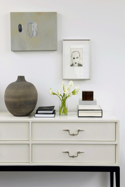 A Japanese raku pot tops a vintage Tommi Parzinger console in the entry.