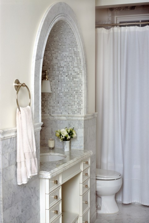 Custom vanity and luxe marble update classic tile patterns, making everyday ablutions feel grandly ritual.
