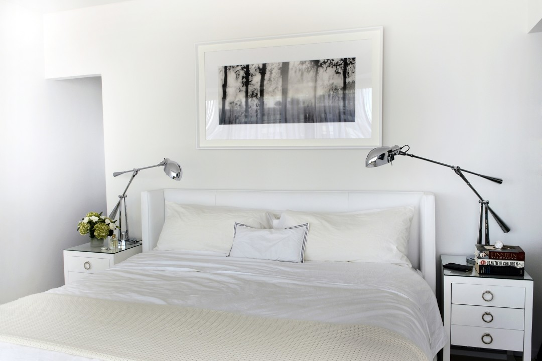 The all-white bedroom helps the couple to relax after days filled with visual stimulation.