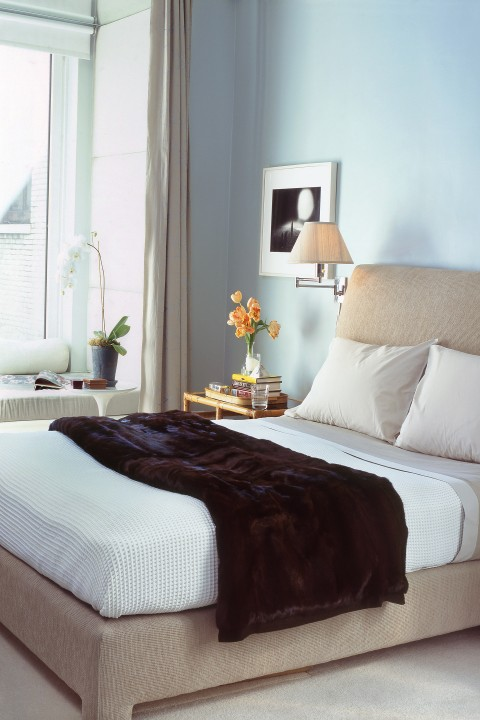 Pale blue walls offset the linen bed and grey silk curtains, enclosing the bedroom in restful quiet and comfort.