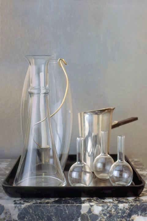 Vintage glassware is luminous against handleafed silver wallpaper.