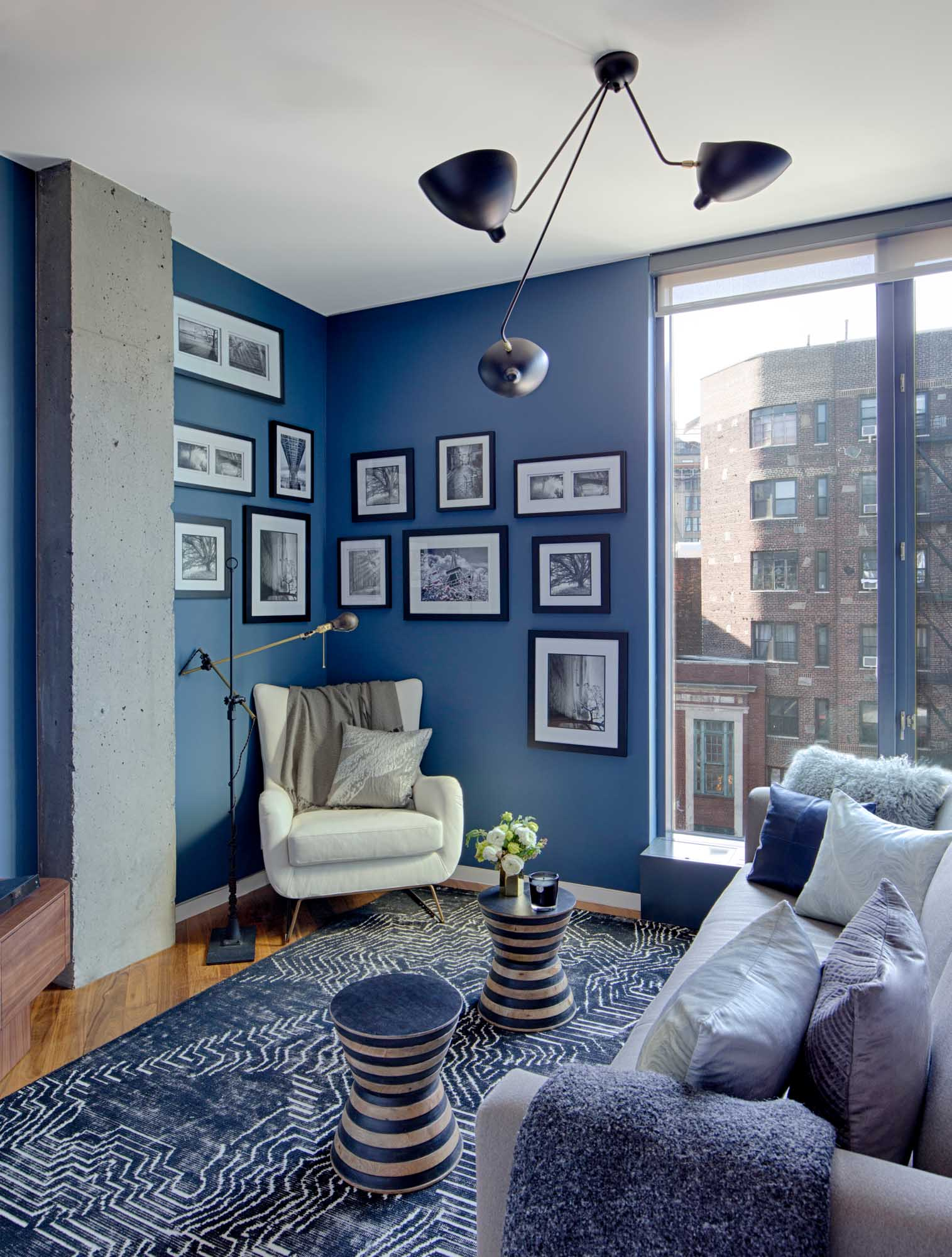modern design living room with white and blue theme, paintings hanging on the wall, stylish lamp on the ceiling and large window