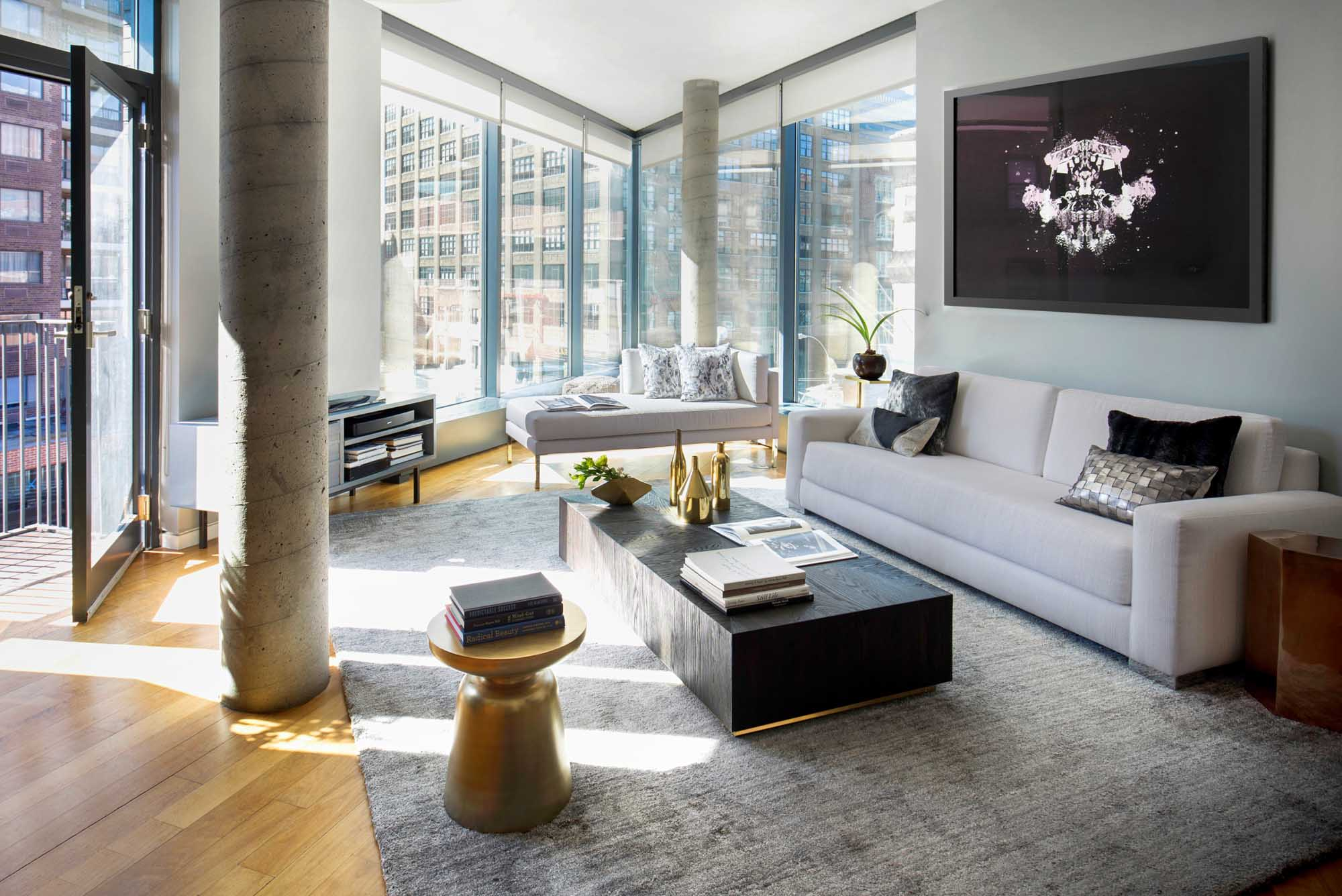 spacious modern living area with stylish black and white pillows on the white sofa, large wooden center table, carpeted floor and wide glass walls overlooking outside