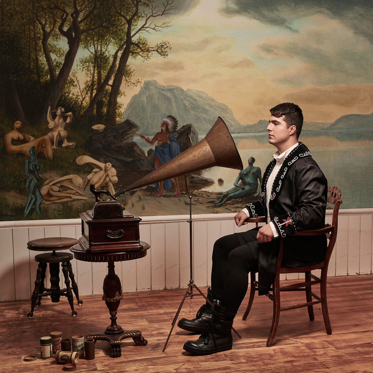 Album art for Jeremy Dutcher's 'Wolastoqiyik Lintuwakonawa' (2018) / (a photo of jeremy dutcher sitting in a chair with arm rests looking into a grammophone. the grammophone is sitting on a small table. there is a stool behind it, and in the background there is a mural of first nations people near a lake.)