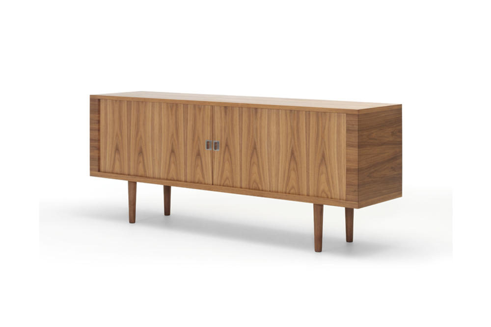 CH825 | CREDENZA   Hans J. Wegner  Although it looks simple, the credenza features an advanced design with roller shutter doors, requiring double sides and rear panel, between which the roller shutters run on a track and disappear when opened.The interior features adjustable shelves and pull-out drawers designed to enable simple installation of additional drawers.