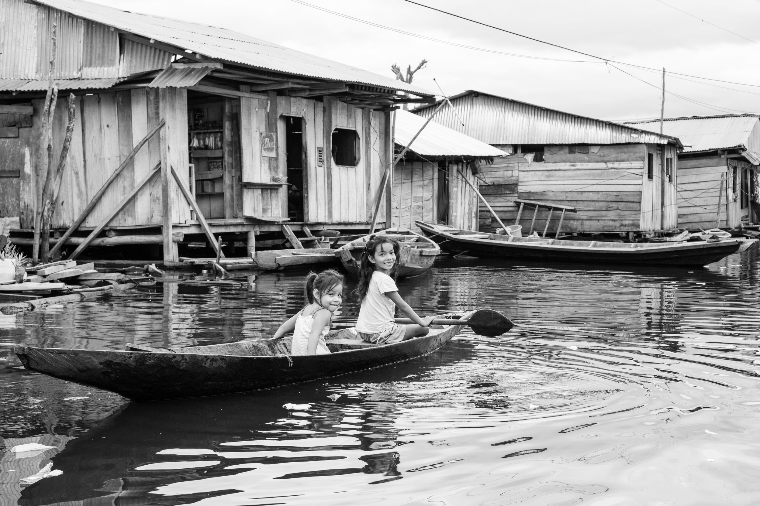 Two young girls paddle a canoe in the flooded village of Belen in Iquitos, Peru.