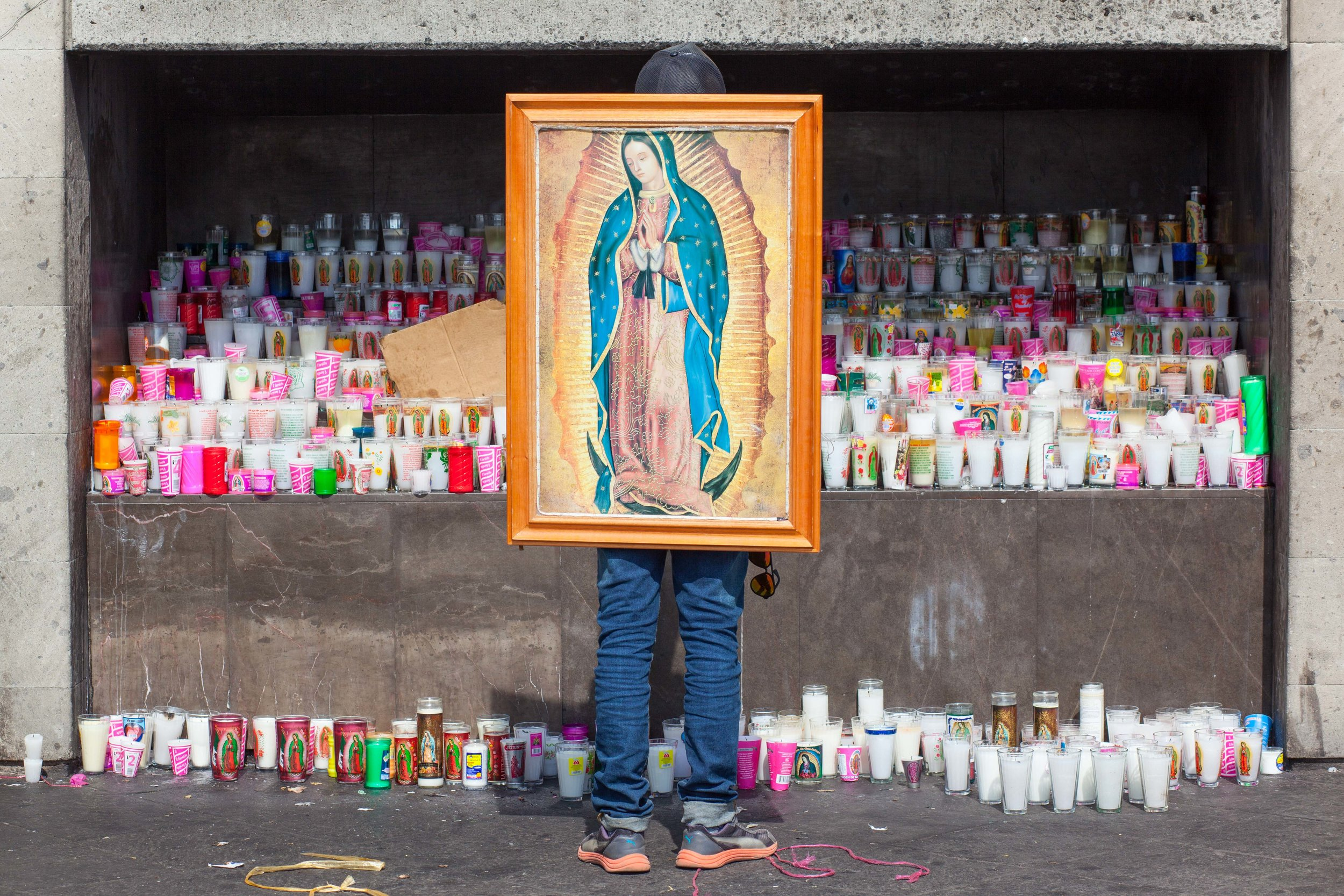 The Pilgrimage to the Basilica of Our Lady of Guadalupe, Mexico City, a man prays against a huge offering of candles.