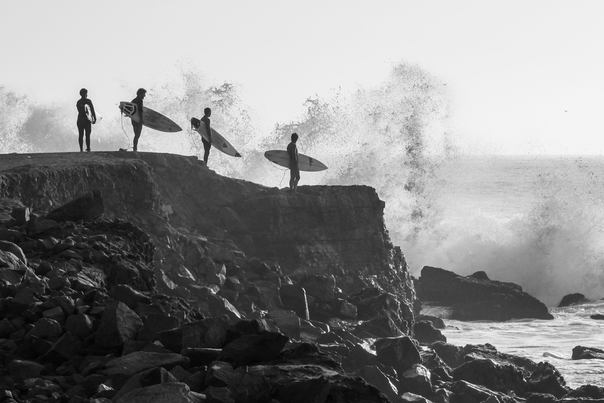 Surfers in Peru in black and white.