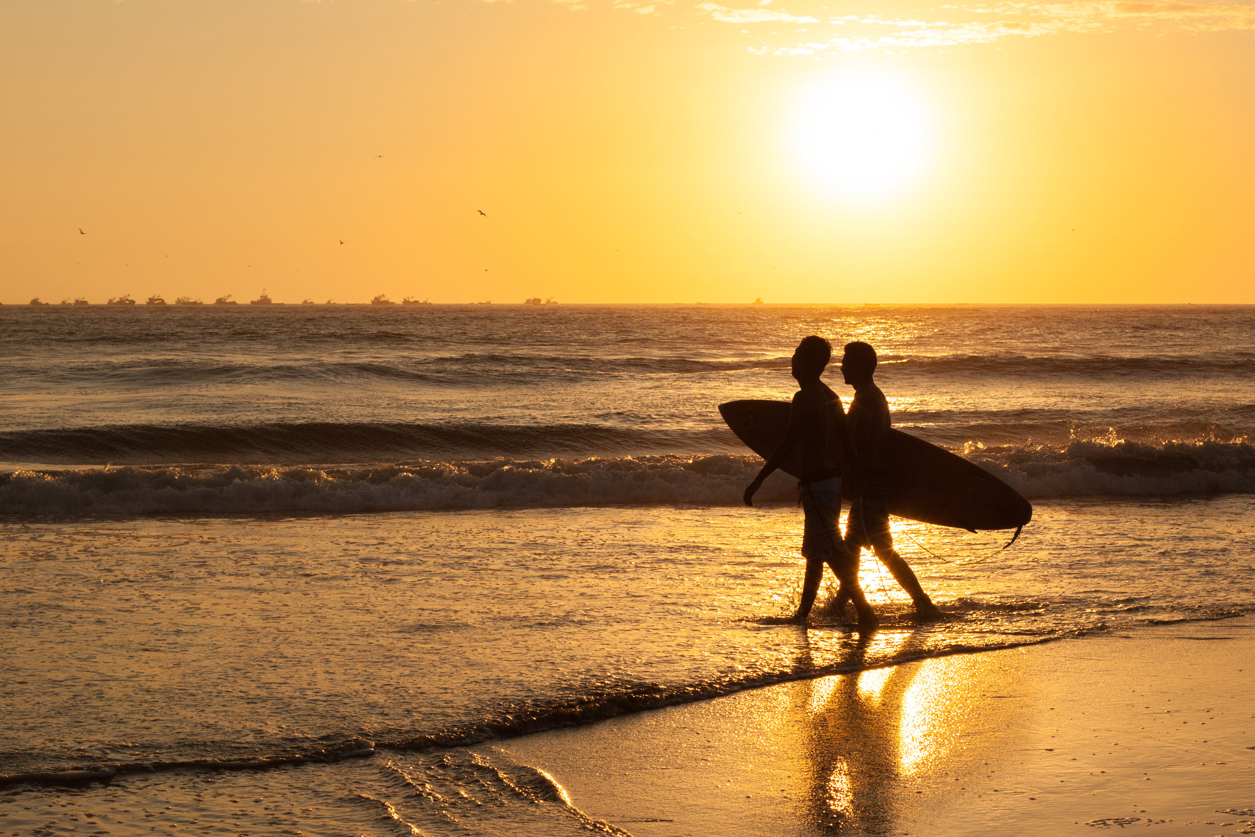 Silhouette photography by Geraint Rowland, two surfers at sunset in Peru