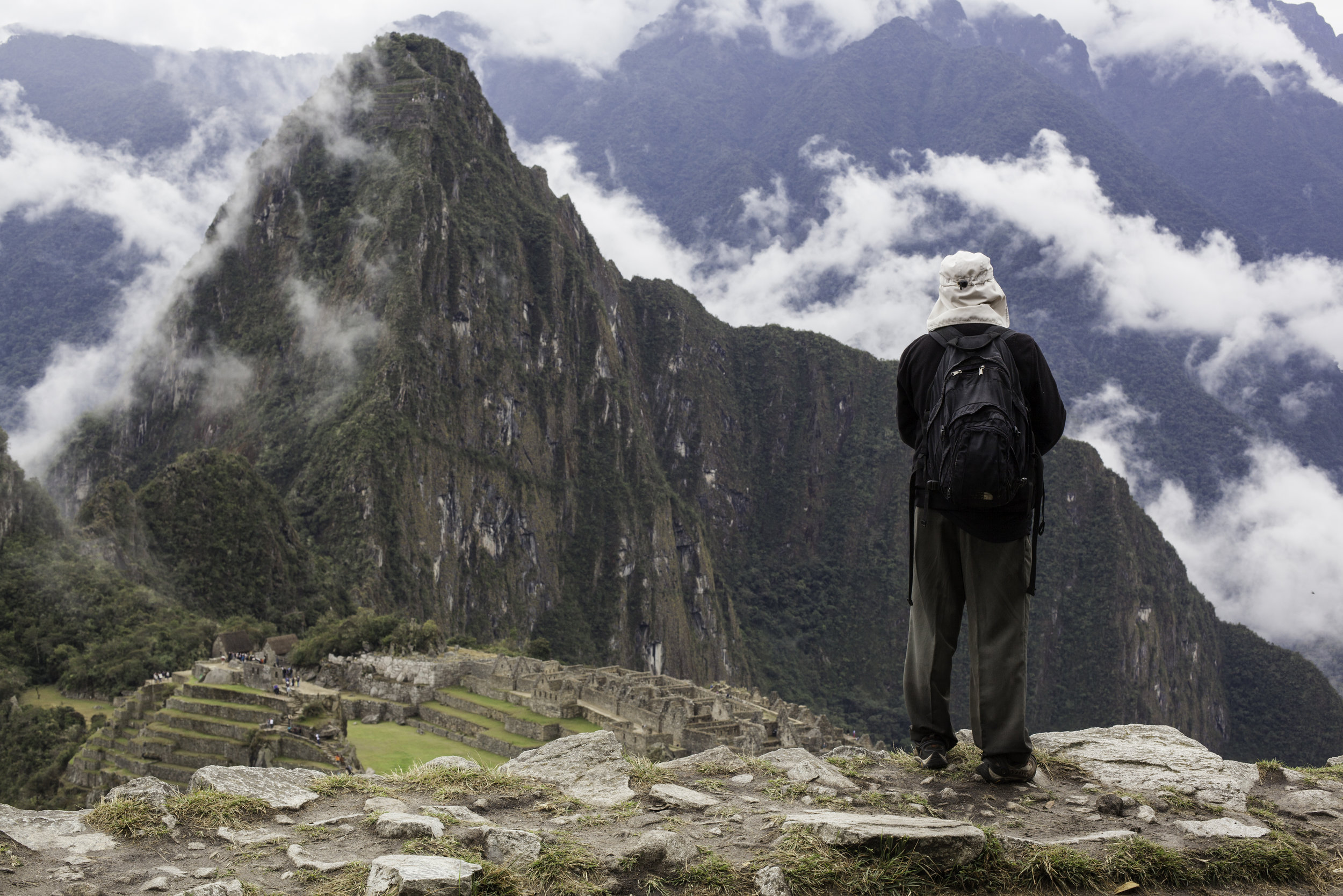 A hiker looks down on the impressive Machu Picchu.