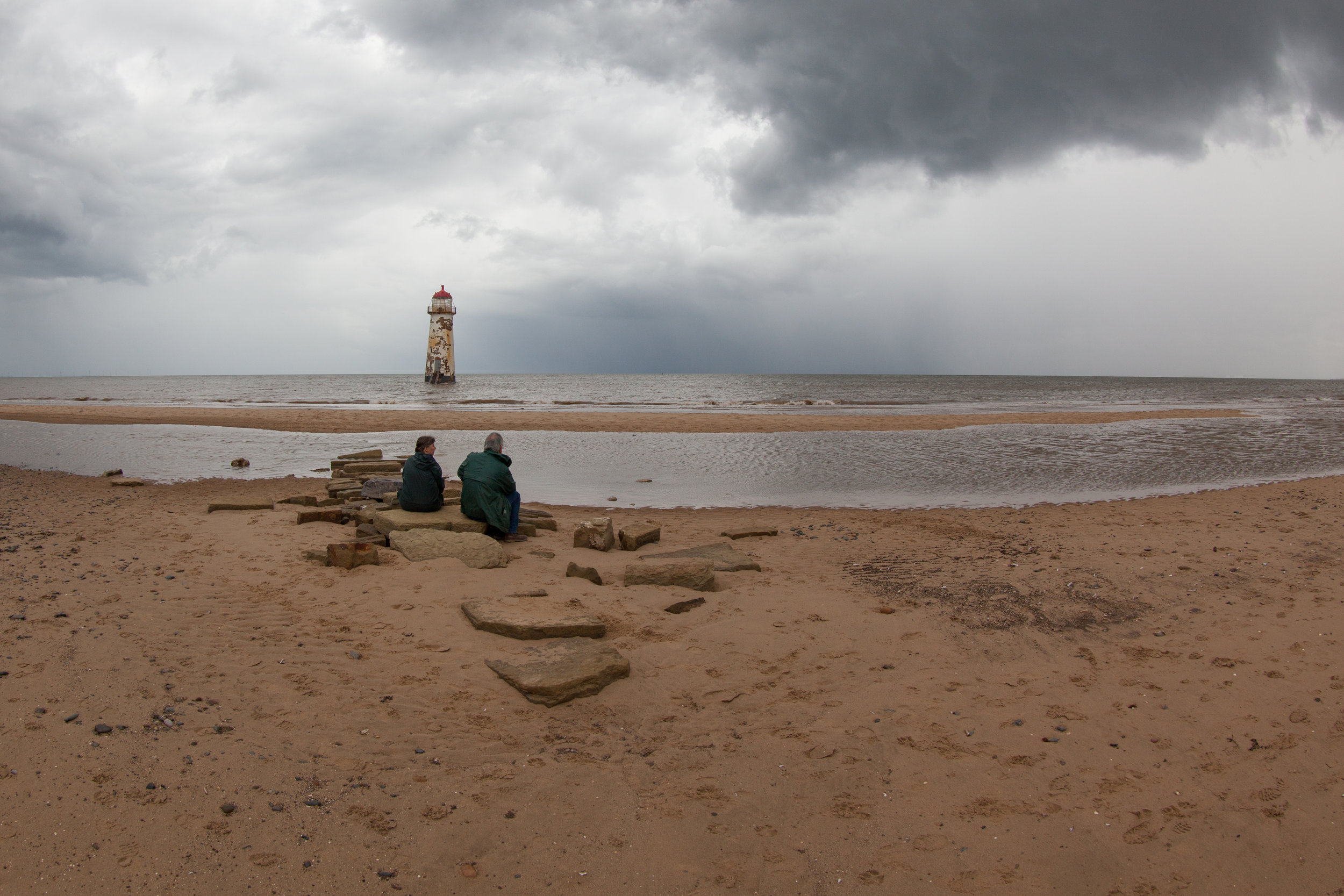 A couple sit on the beach in North Wales in front of the Talacre Lighthouse.