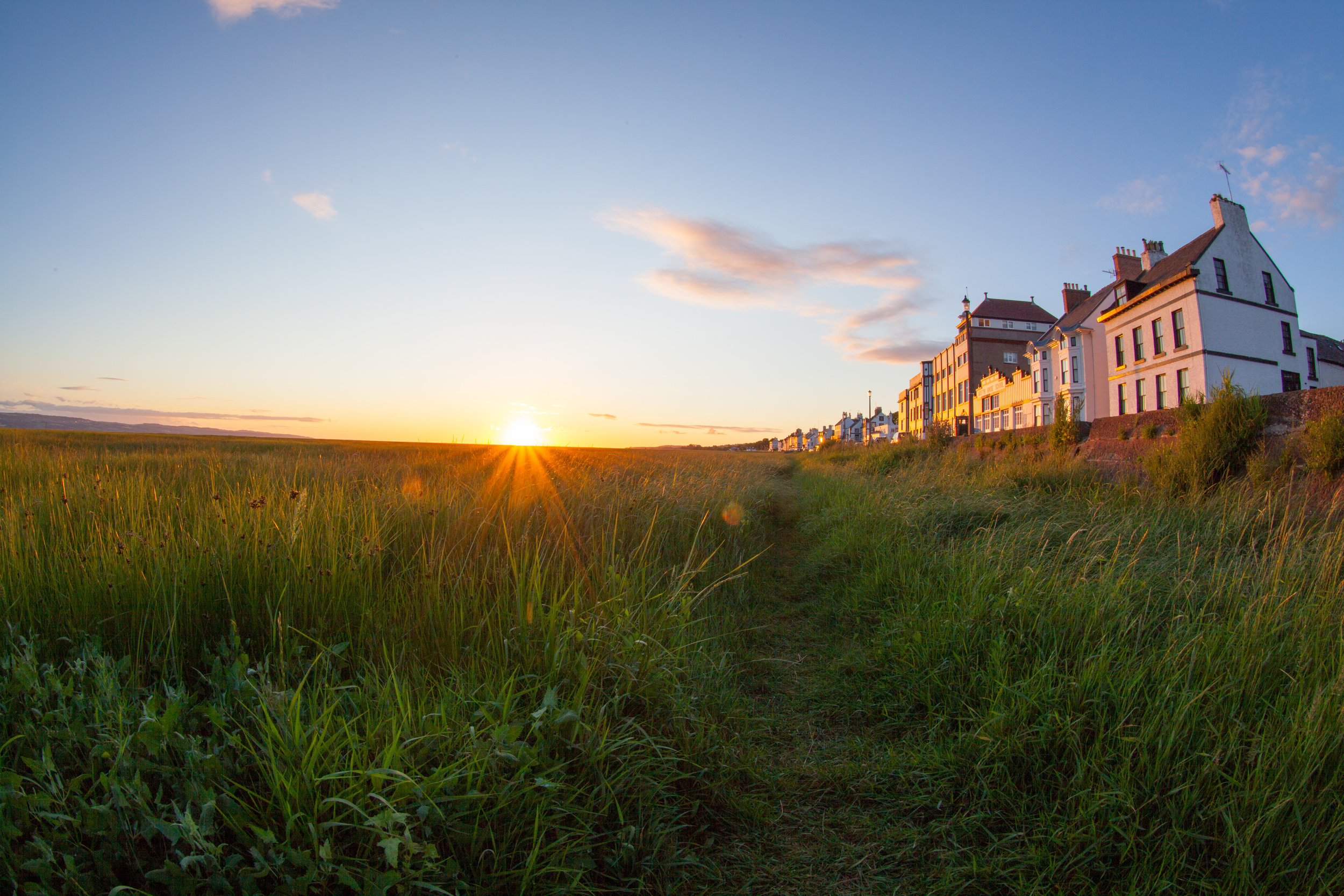 The sun setting over a field and the seafront of Neston in England.