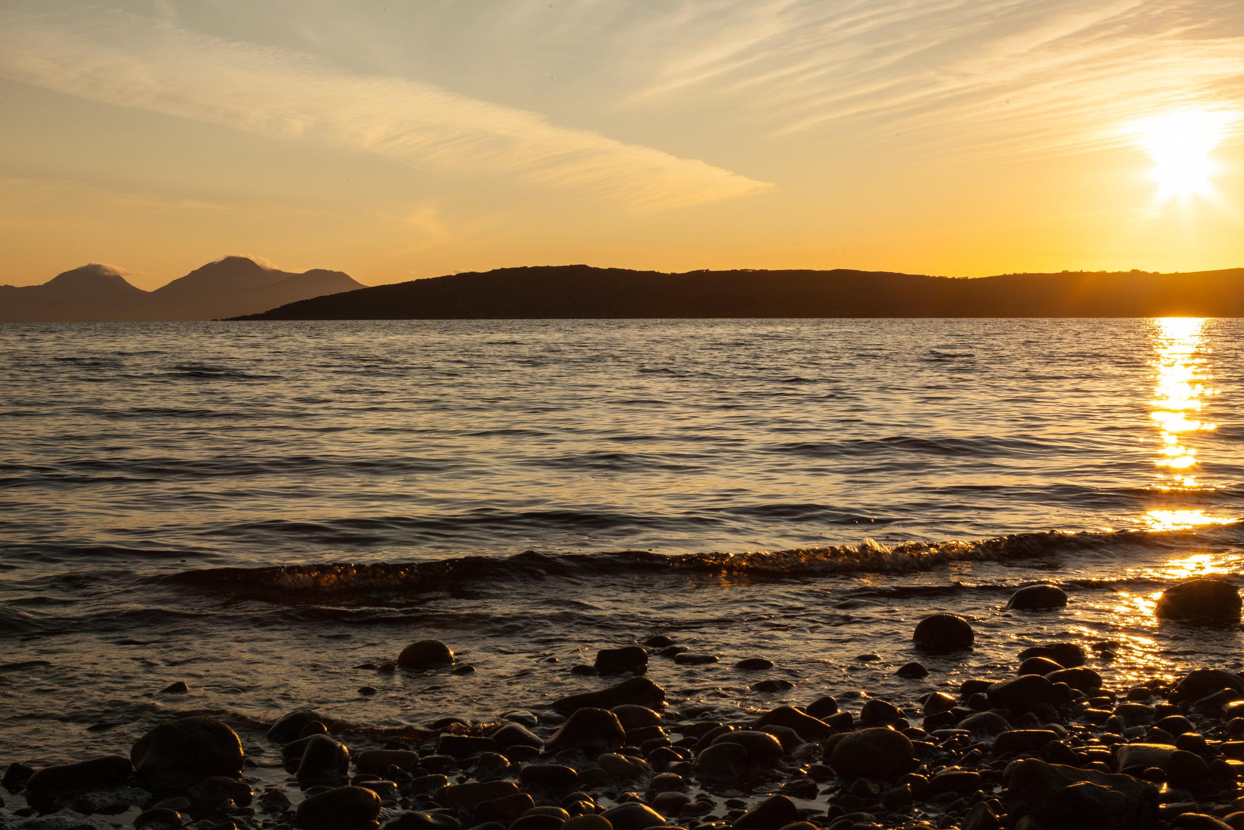 A golden sunset ove a loch in Scotland.