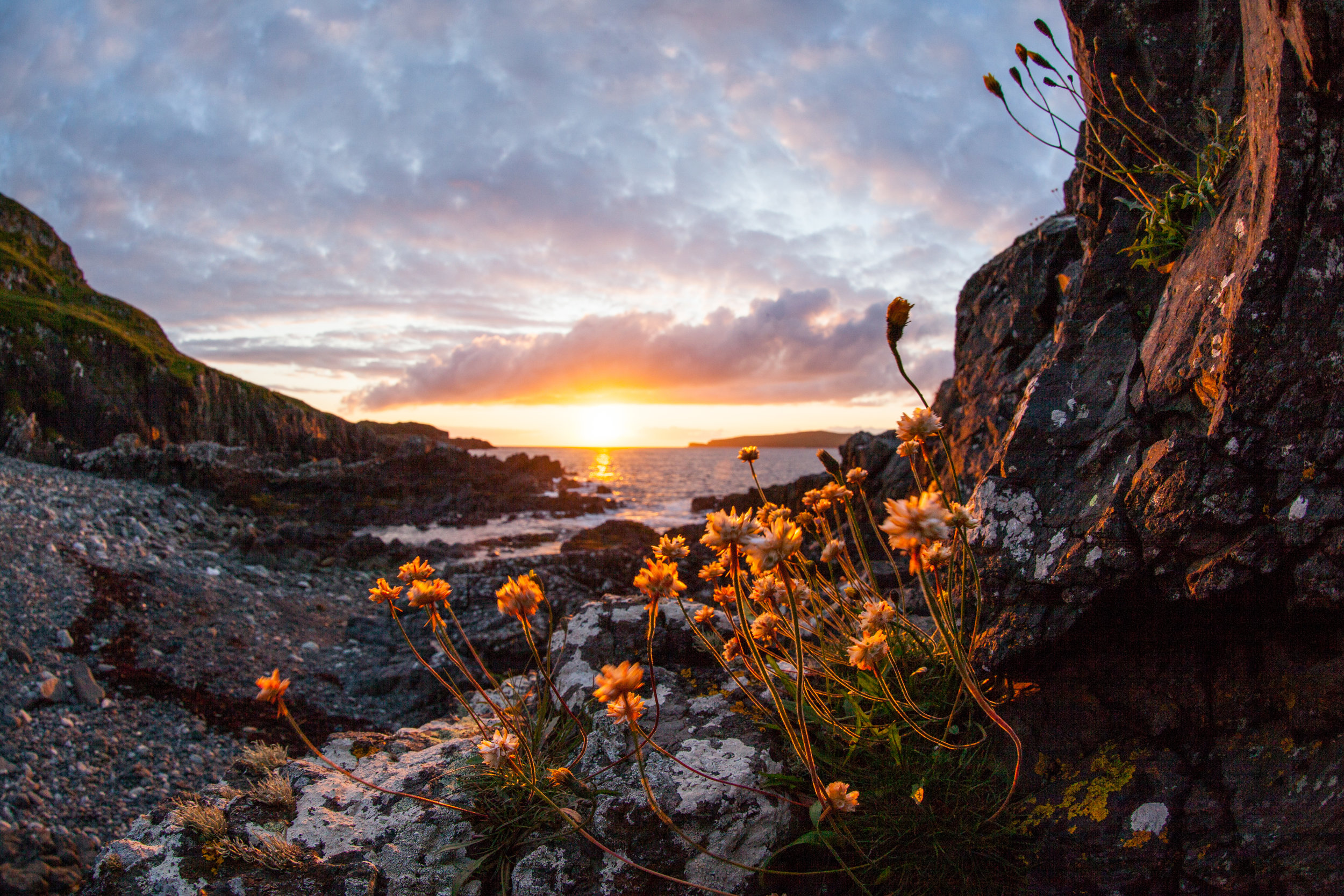 A beautiful fish eye style of the sun setting over a beach in Scotland.