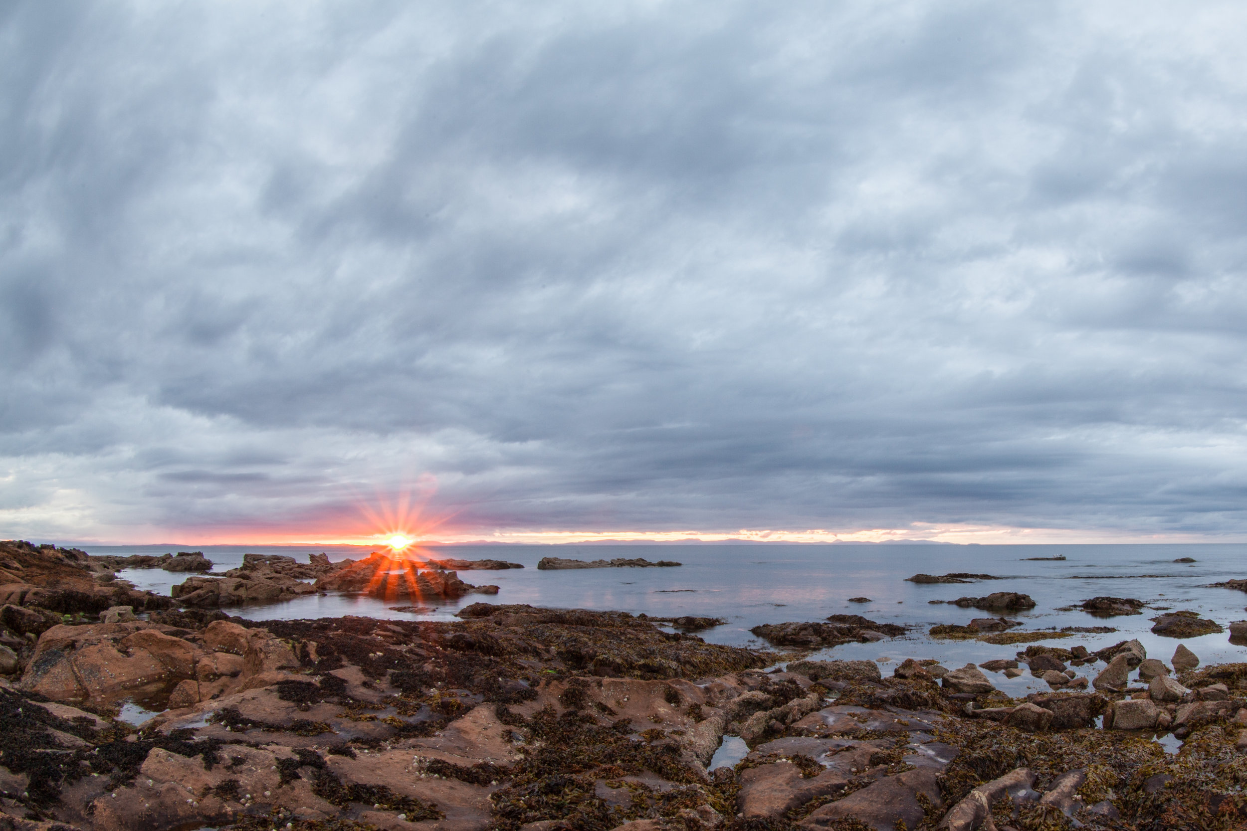 A wide angle sunset photo from the coastline of Scotland.