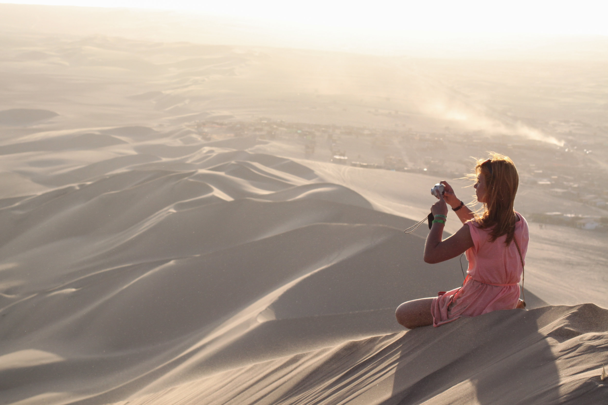 A red head girl sits on one of the largest sand dunes in South America to enjoy the sunset in Huacachina, Ica, Peru.