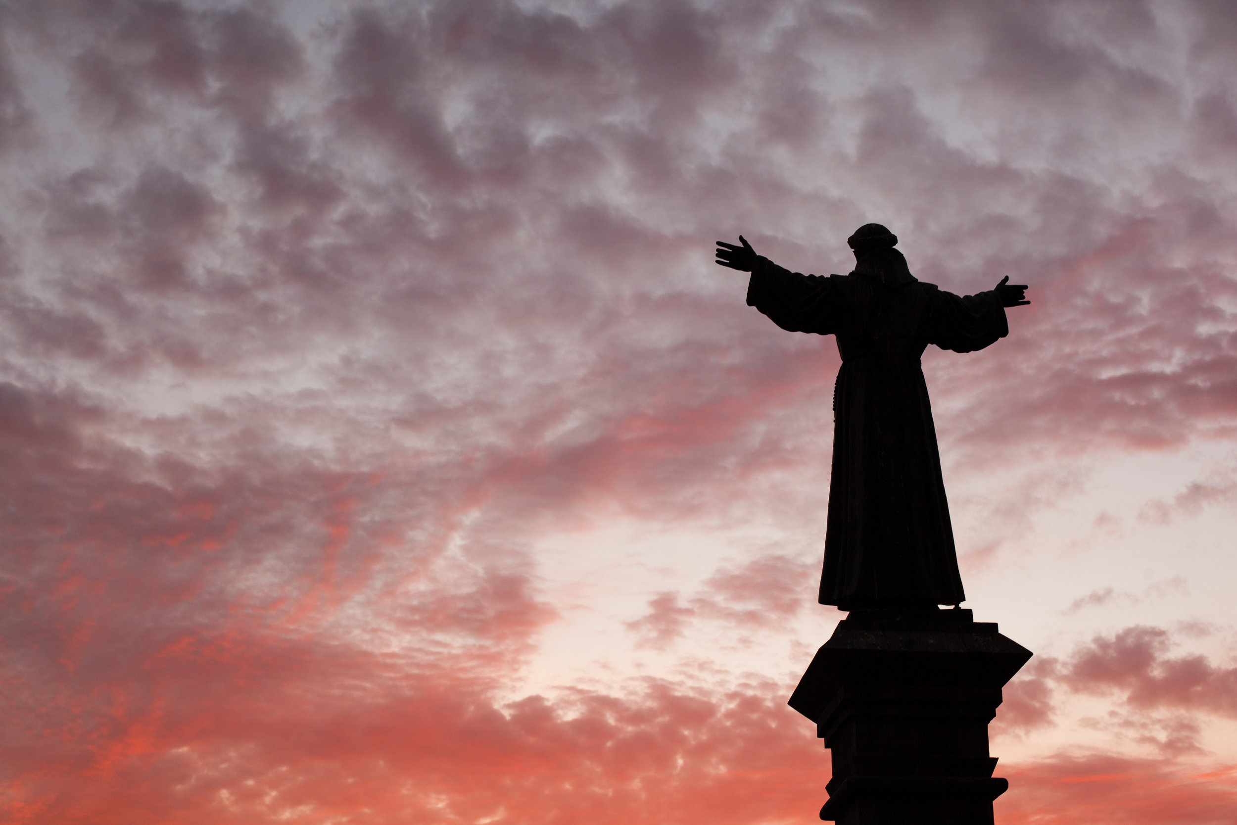 A blood red sky behind a religious statue in Arequipa, Peru.