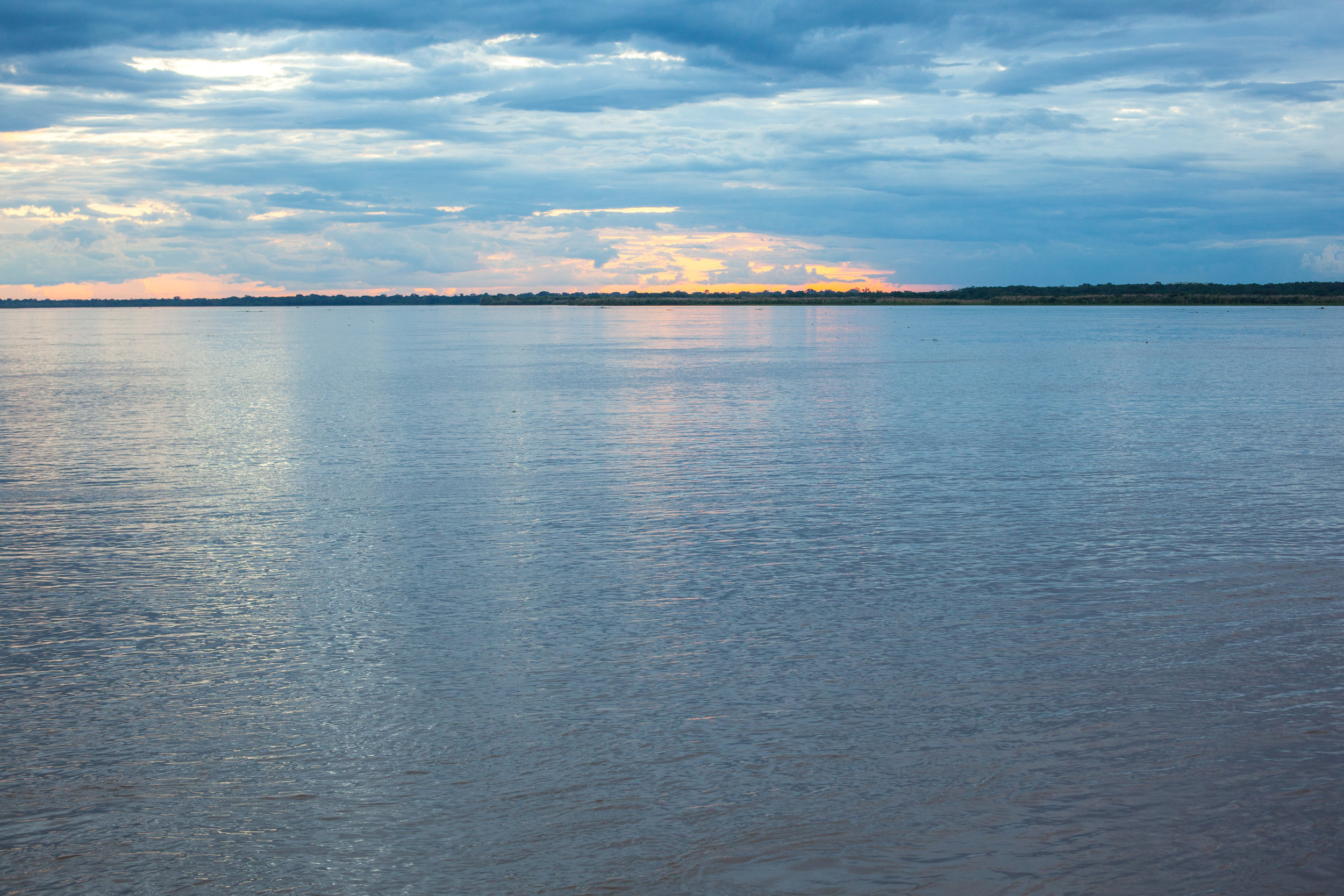 A calming photo of the Amazon river in Peru at sunset.