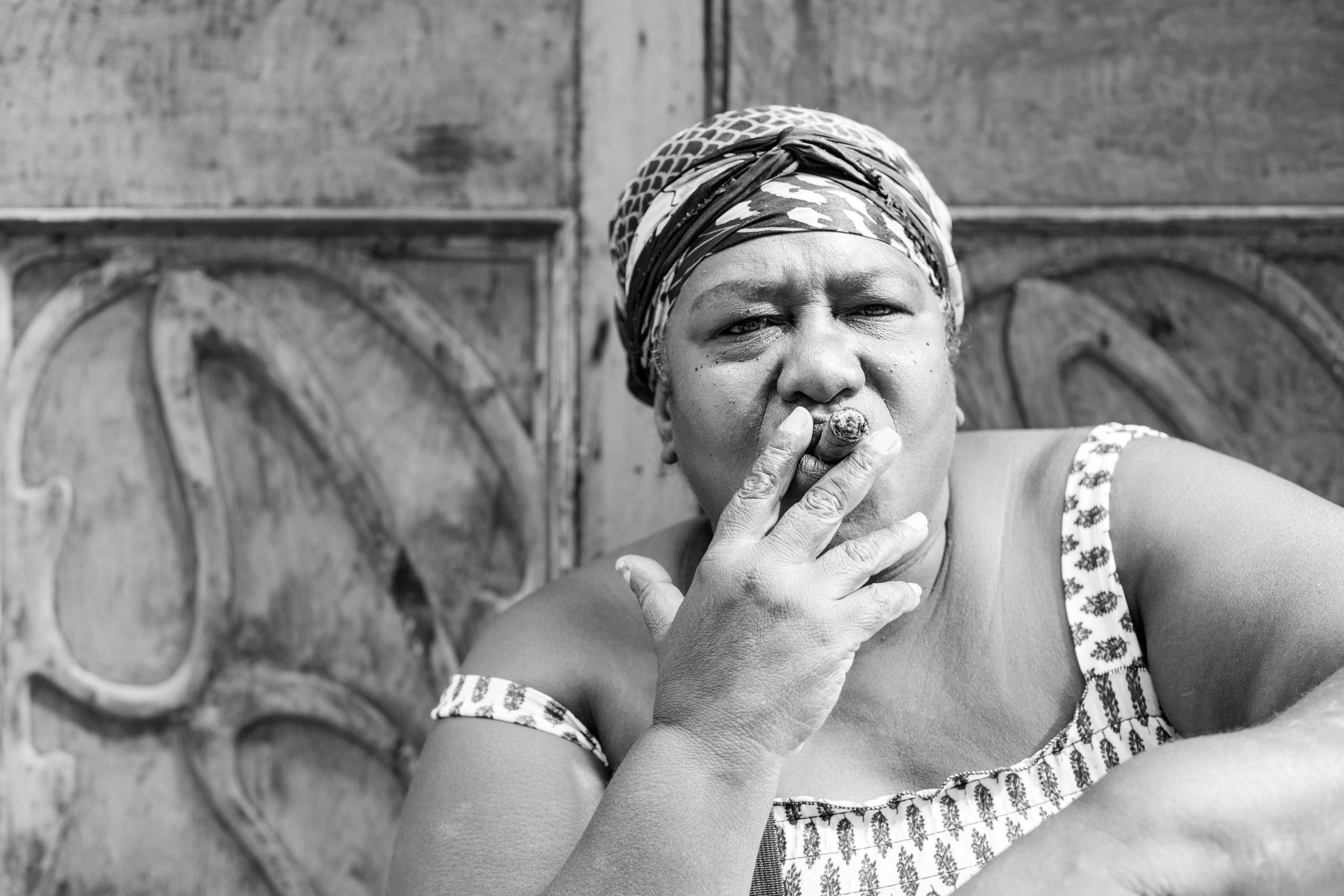A black and white portrait of a curvy Cuban lady smoking a cigar.