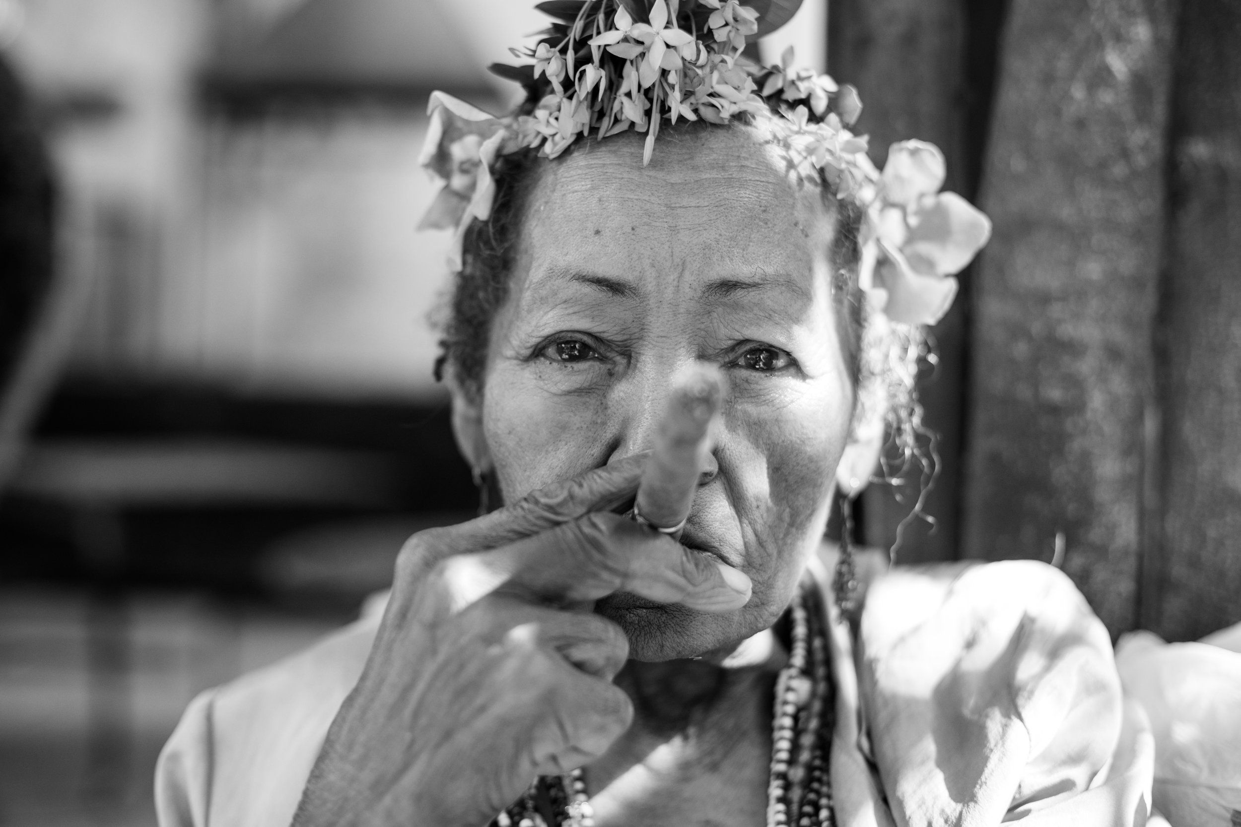 A black and white portrait of an elderly cuban lady with flowers in her hair and a large cuban cigar.