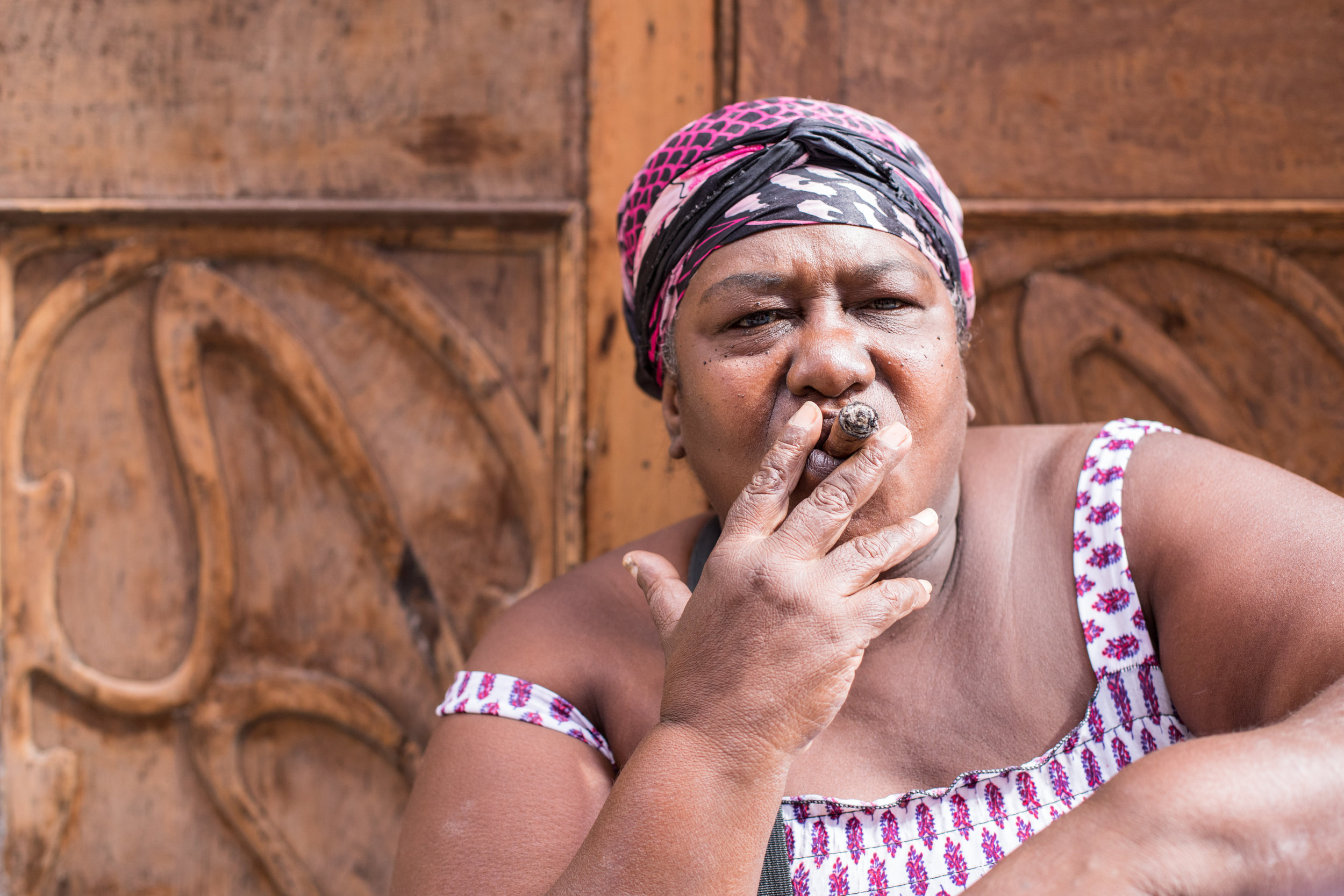 A large Latina women smokes a cigar on the streets of La Habana, Cuba.