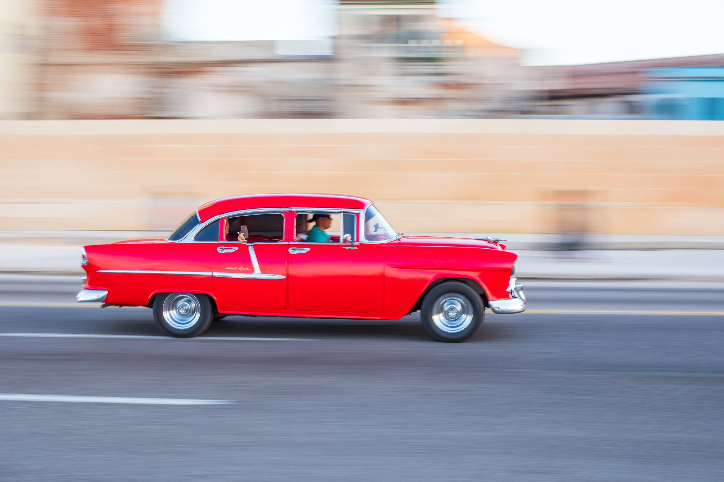 A beautiful red 55 chevy classic car drives along the malecon in Havana, Cuba.