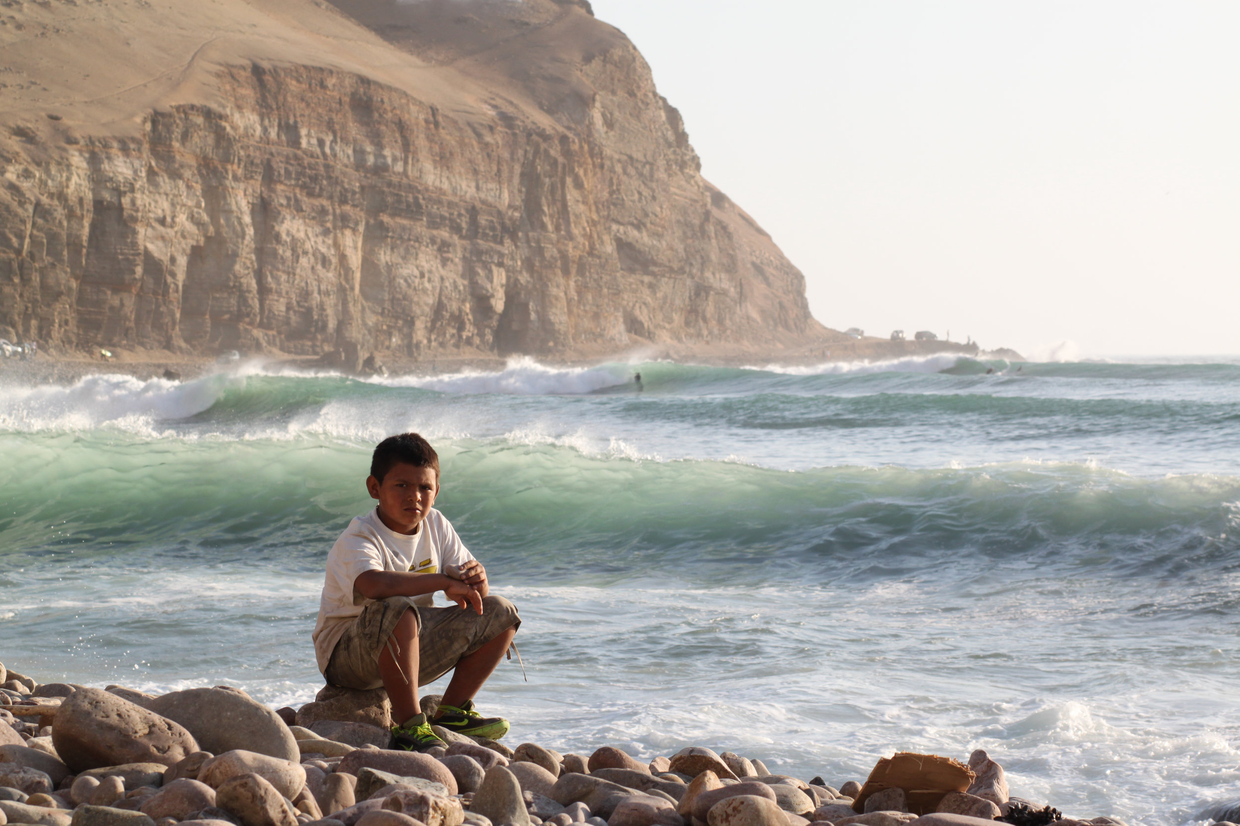 A boy sits on the shore of La Herradura, Lima, while waves are surfed in the distance.