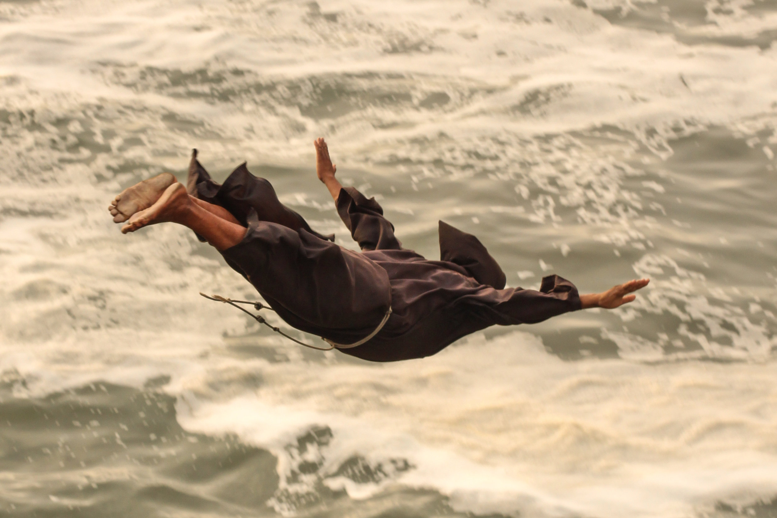 A Monk dives into the water below at El Salto de Fraile, Chorillos, Lima, Peru.