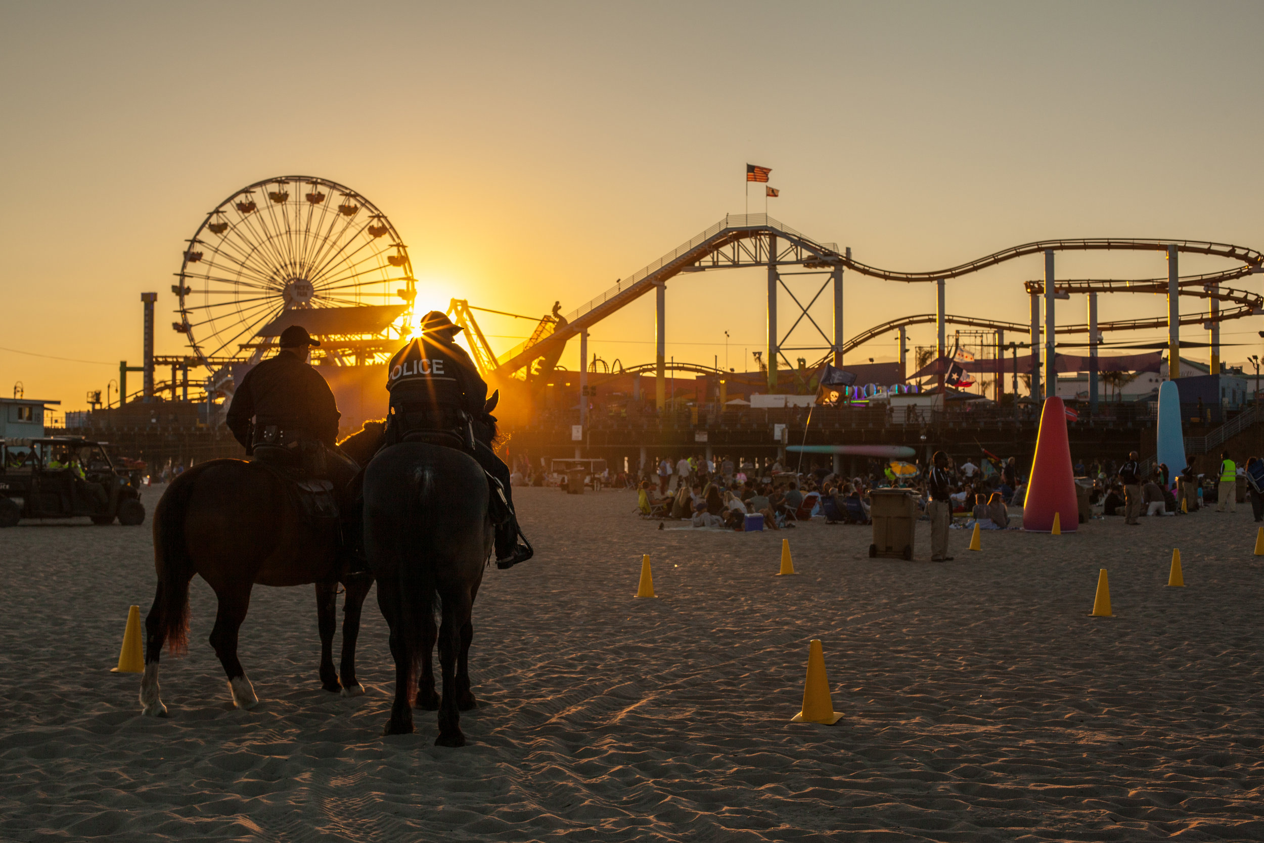 Police on horseback on the beach at Santa Monica with the famous pier in the background.