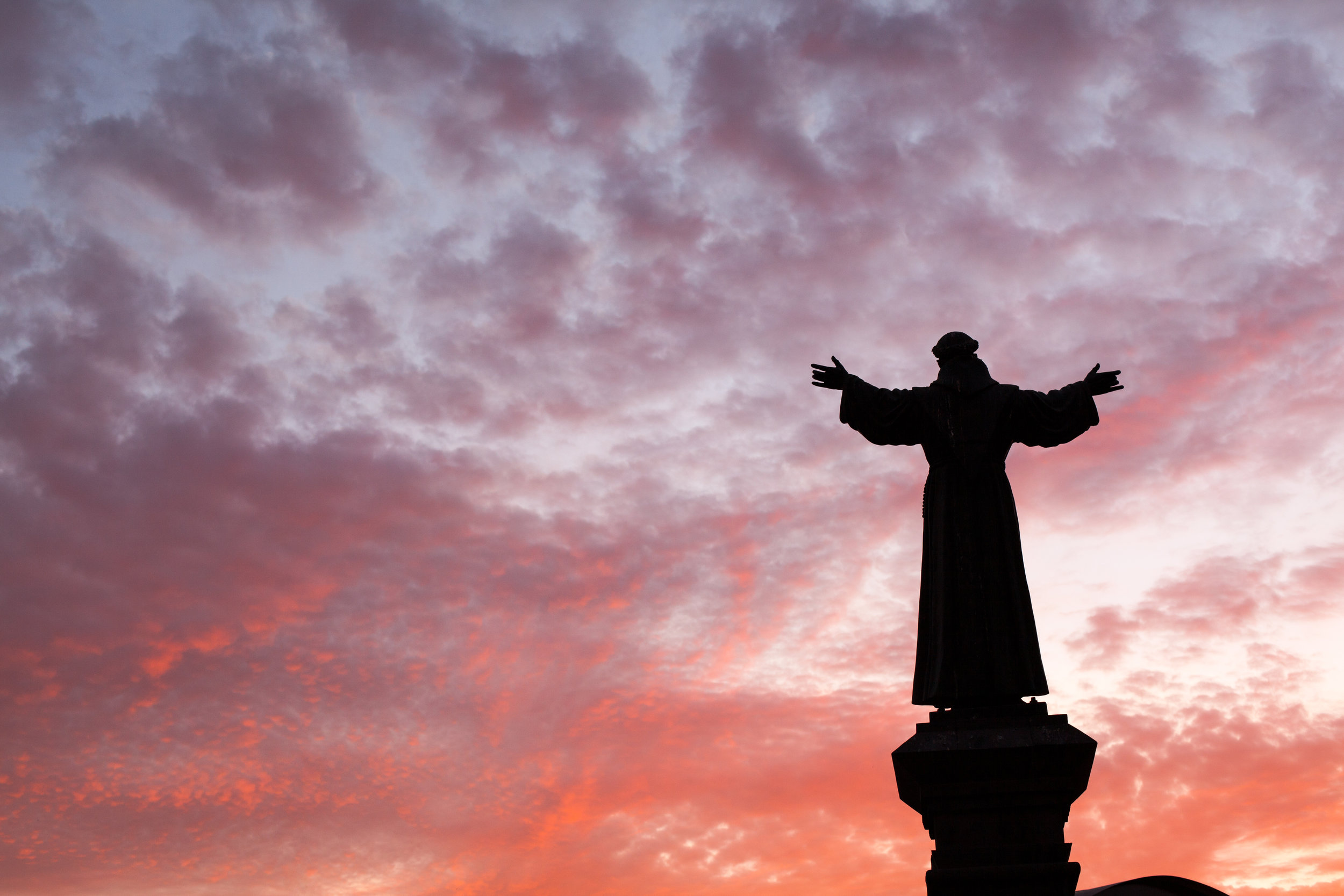Negative space can add drama to an image such as this religious statue against a blood red sunset in Arequipa, Peru.