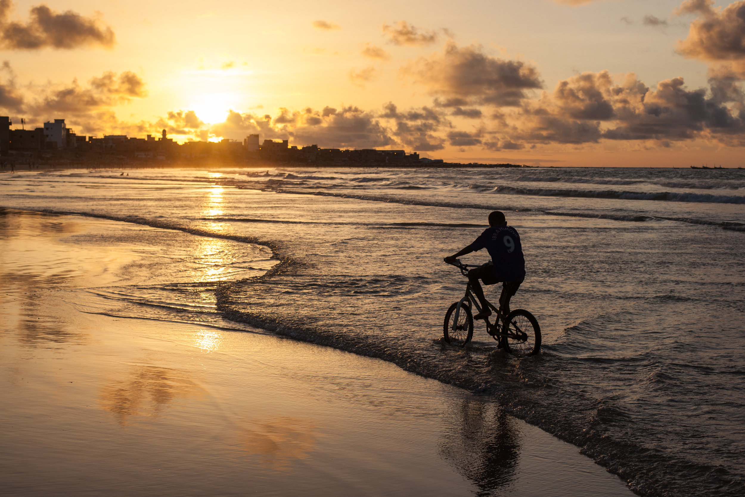 A boy rides his BMX bike along Yoff beach in Dakar at sunset.