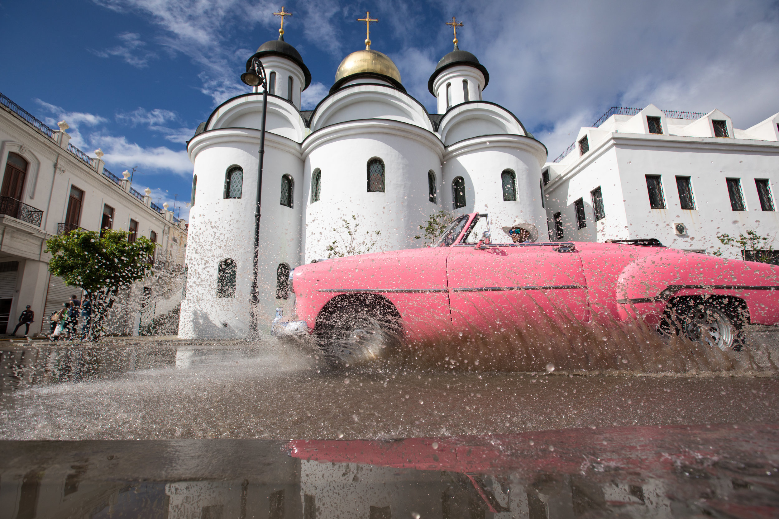 1.  Classic pink car in front of an orthodox church in Havana, the capital of Cuba.