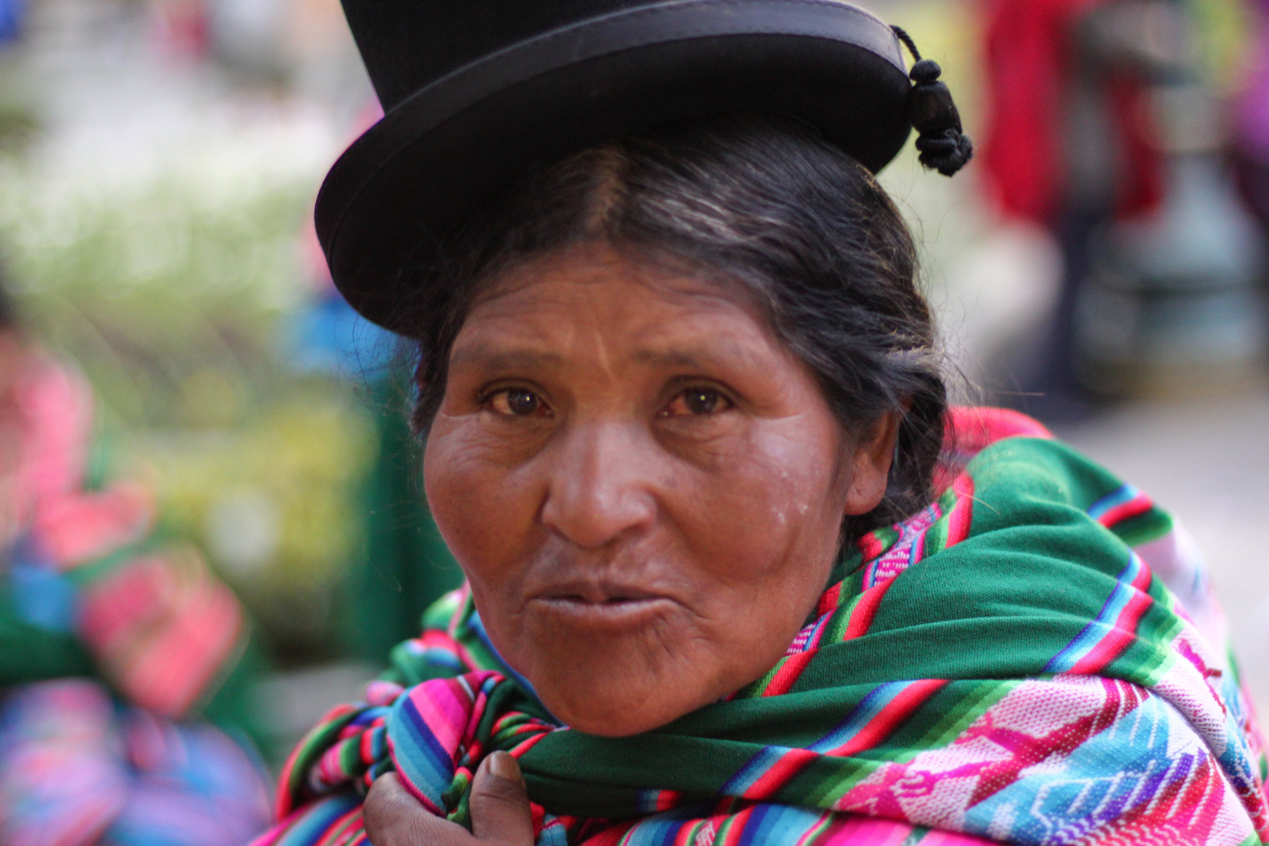 A candid portrait of a traditionally dressed Bolivian woman.