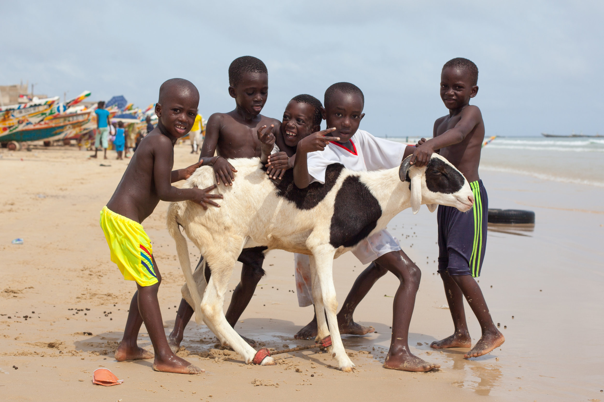 Children pose for a photo with a sheep before the Tabaski Festival on a beach in Dakar, Senegal.