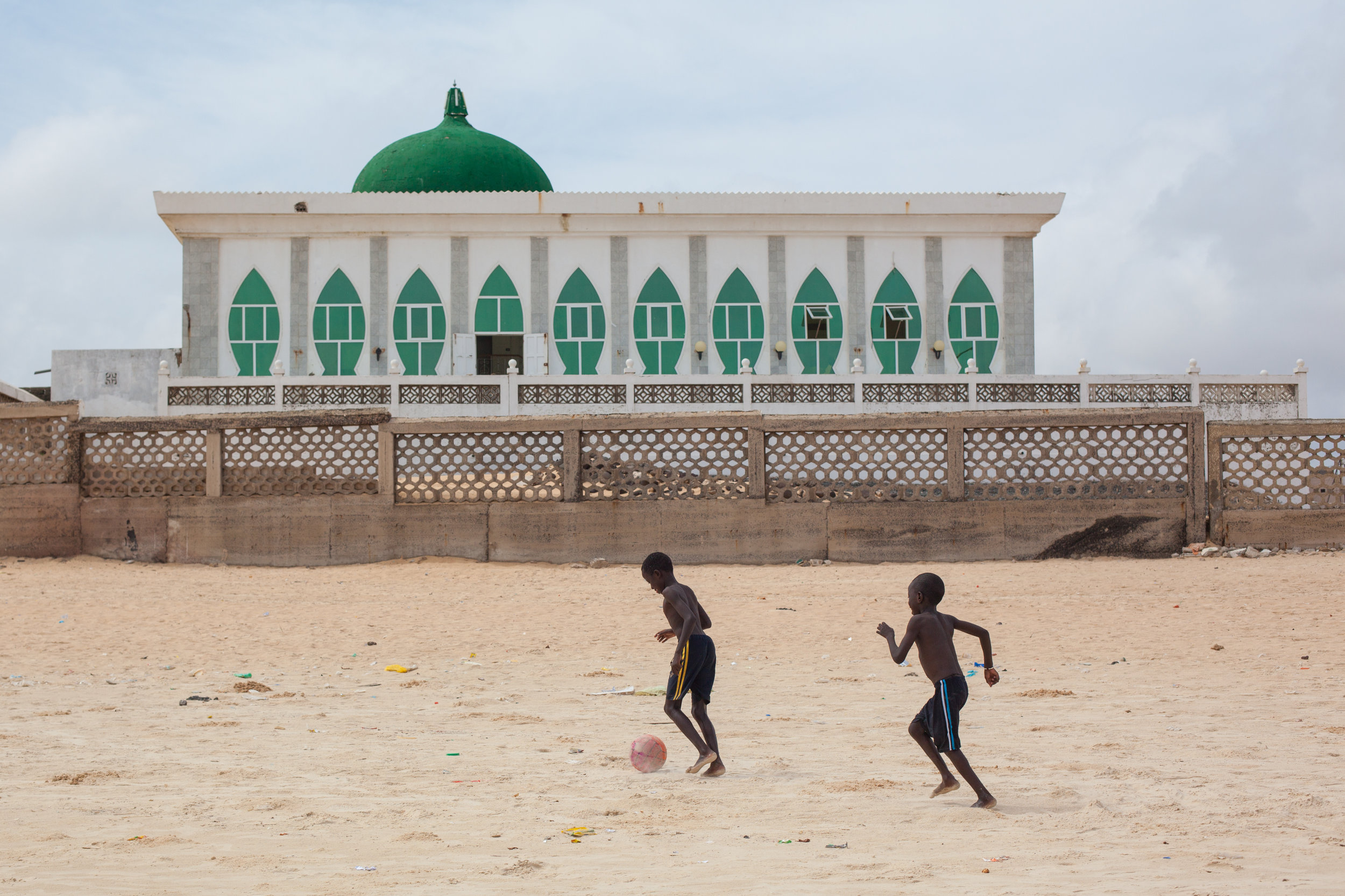 Boys playing football on a beach in Dakar in front of the Grande Mosquée de Yoff.