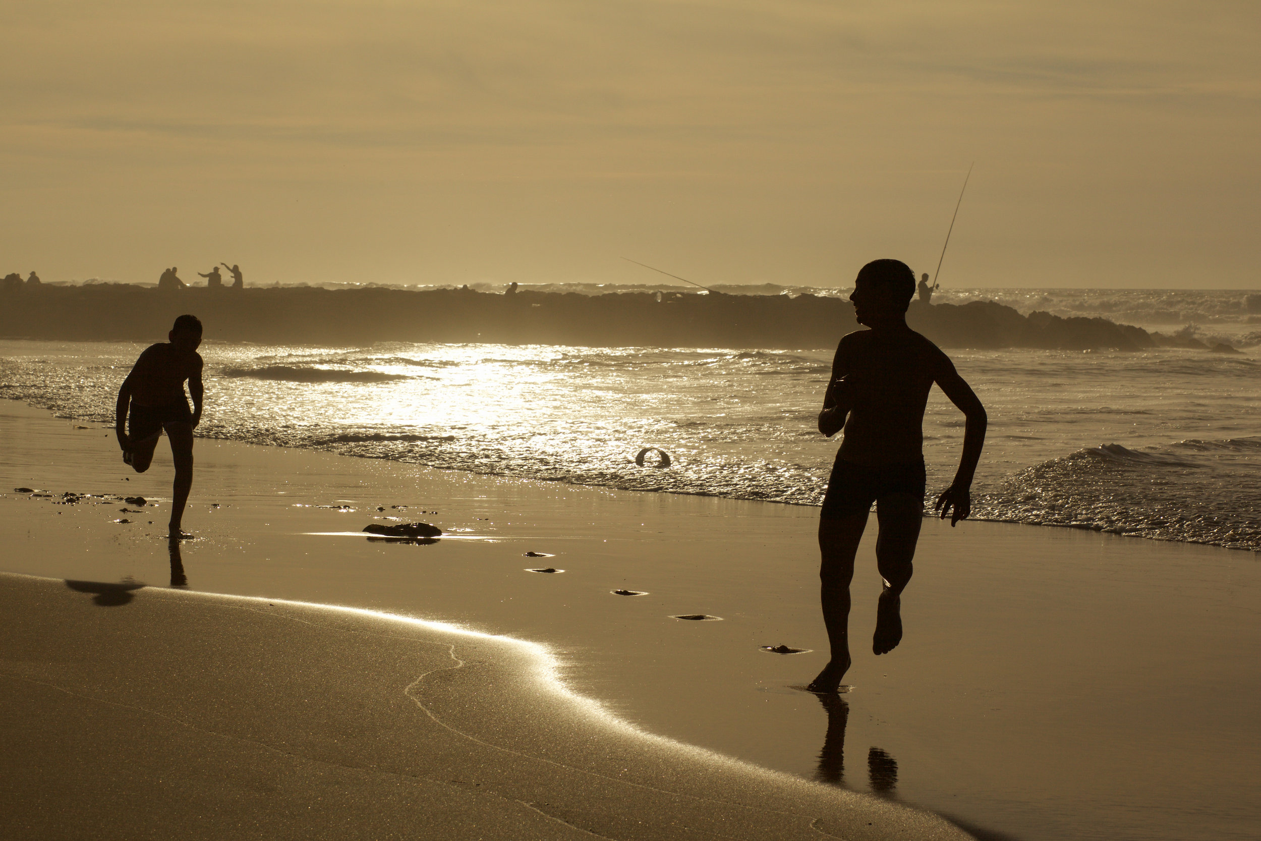 Locals playing on the beach at Casablanca while the sun sets.  A silhouette style image.