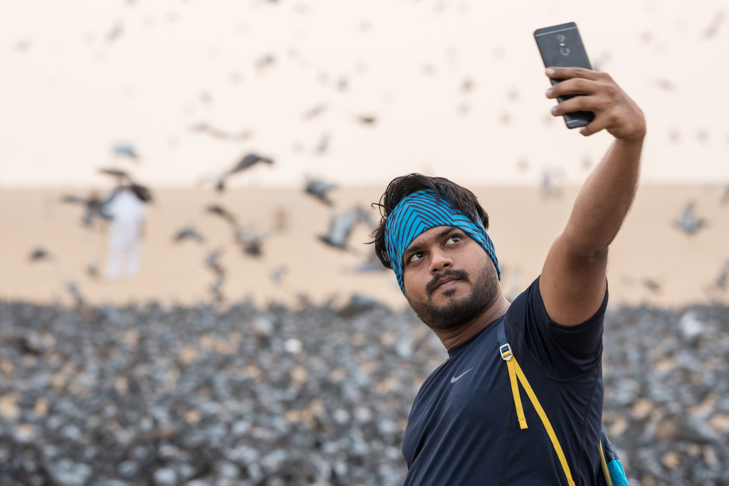 An Indian Man takes a selfie in front of feeding birds on the beach at Chennai.